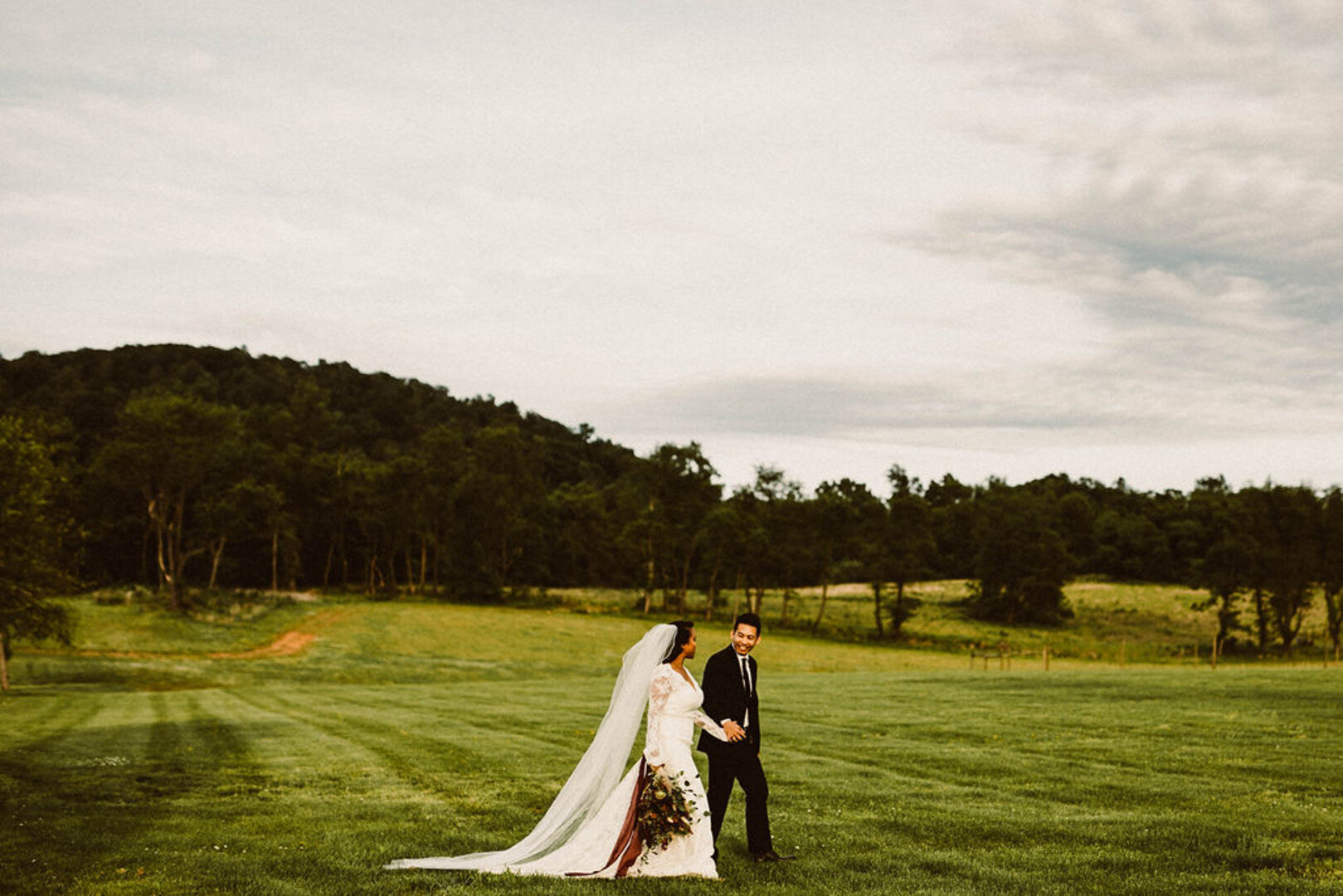 gorgeous bride and groom in open green area