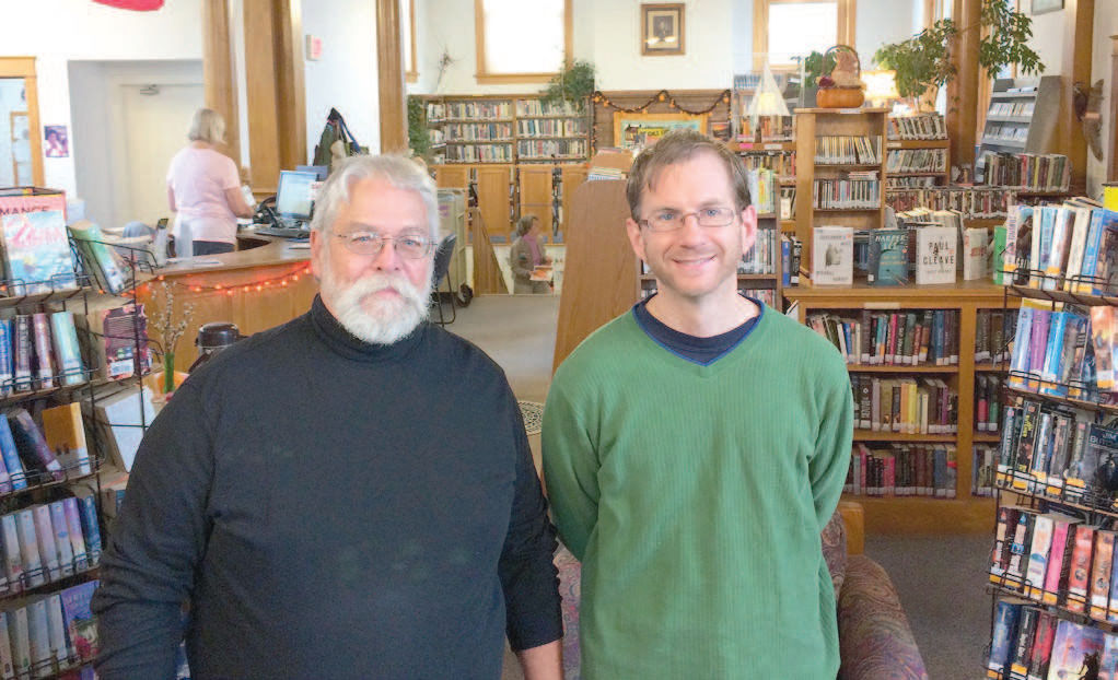 Don Albrecht (left), president of the Bayfield Carnegie Library board, and Blair Nelson, library director, surrounded by different styled bookcases to be replaced in 2016.