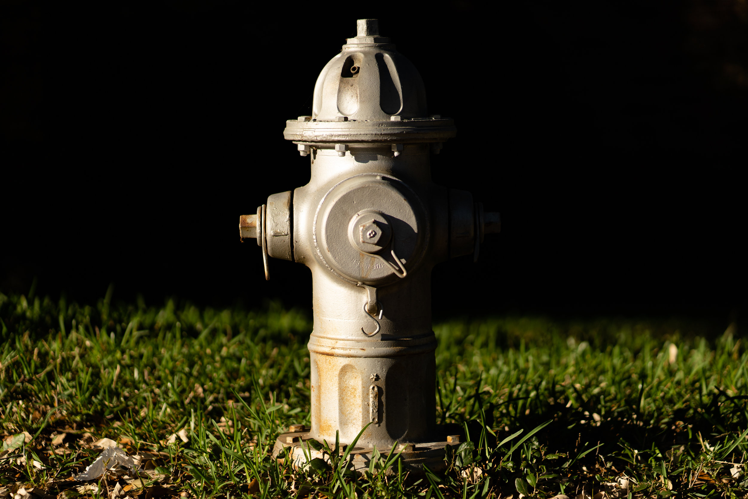 This was made with an 85 mm lens on a full-frame camera. The shadow in the background is brought much closer, so you cannot see what is behind the fire hydrant.