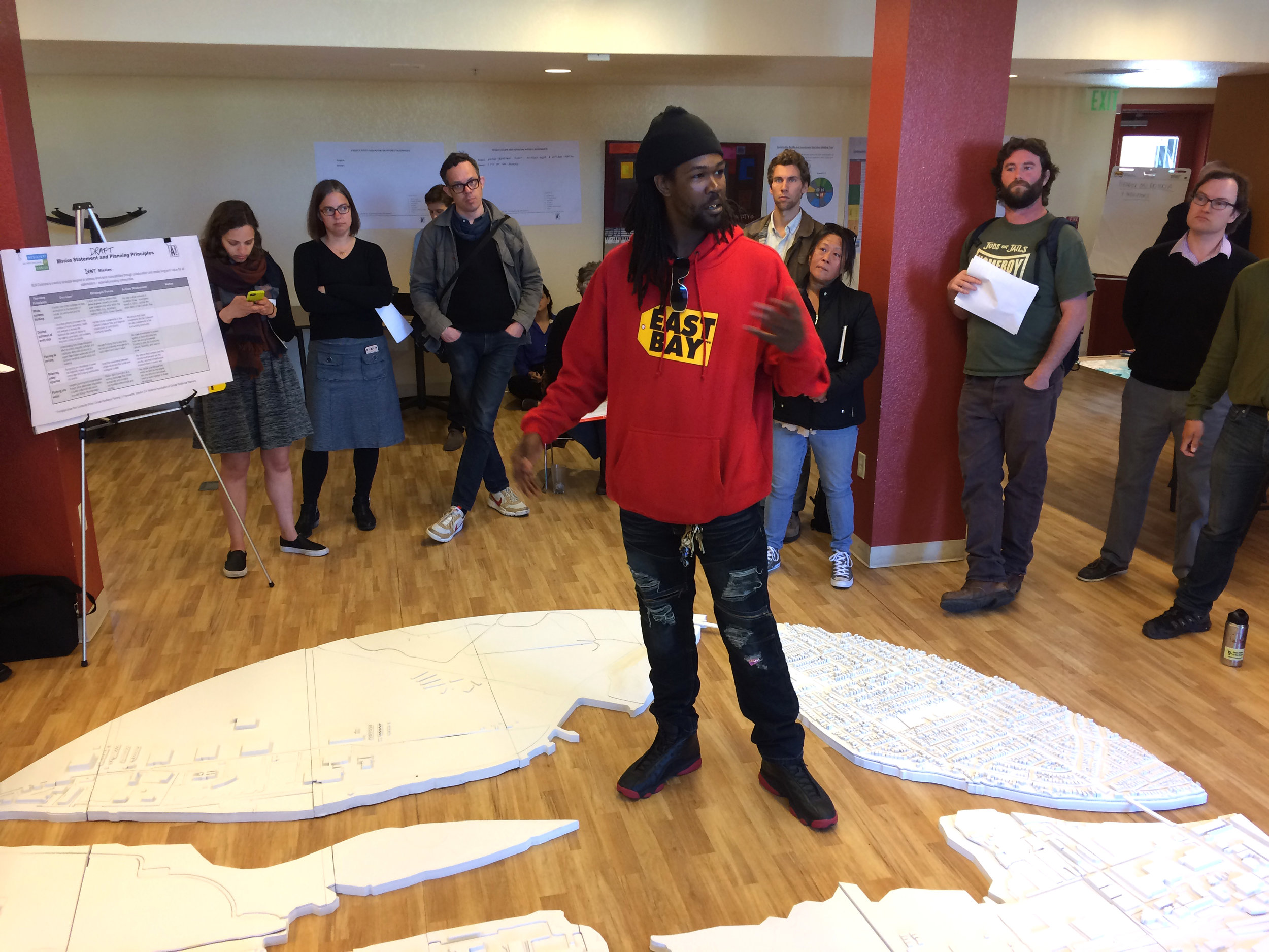 "Reginal ""RB"" Burnette Jr. of the Scraper Bike Team at a Project Working Group meeting, using a model of the Estuary built by Neeraj Bhatia's Reformatting Land studio as a stage. Image: The All Bay Collective."