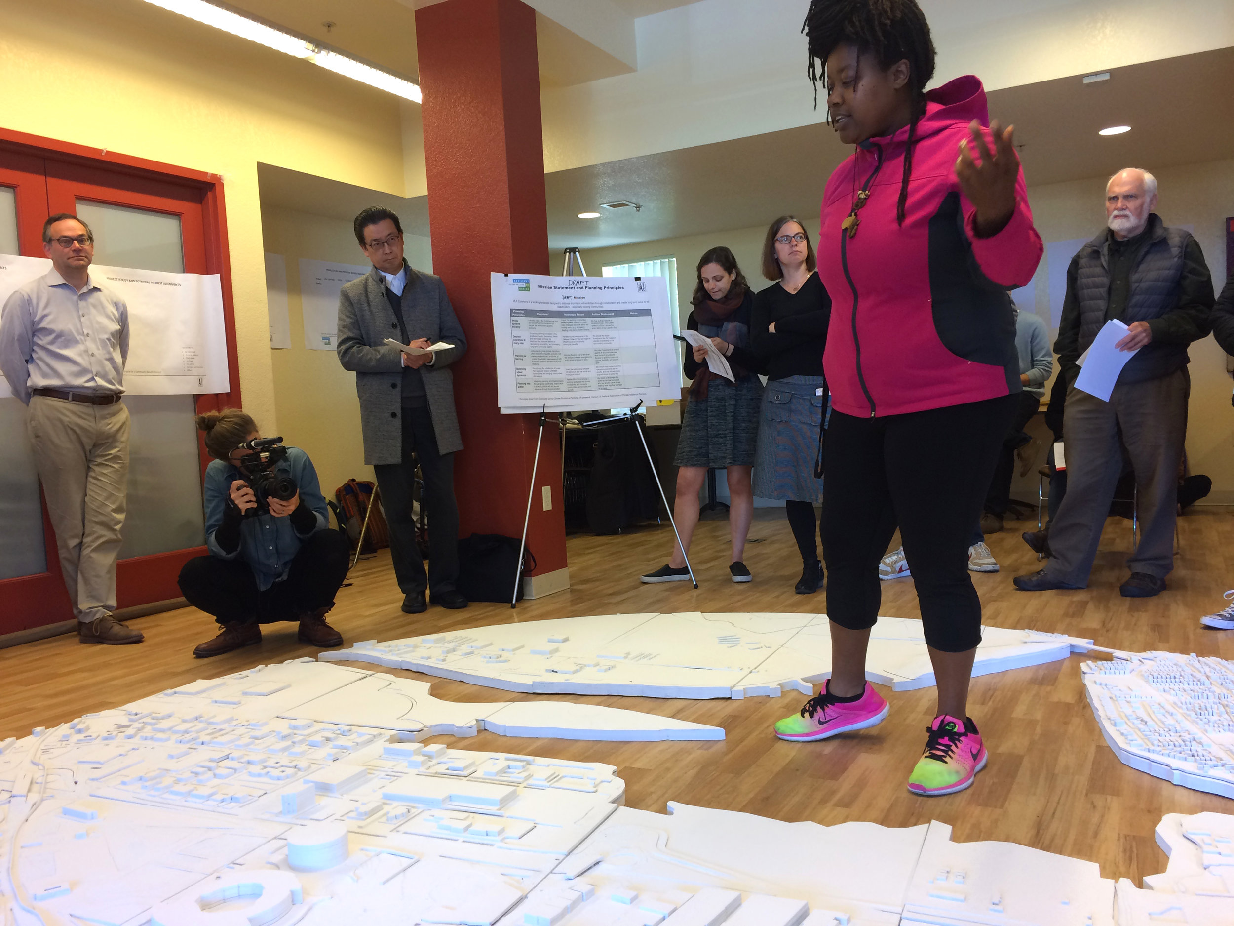 Marquita Price of the East Oakland Collective at a Project Working Group meeting, using a model of the Estuary built by Neeraj Bhatia's Reformatting Land studio as a stage. Image: The All Bay Collective.