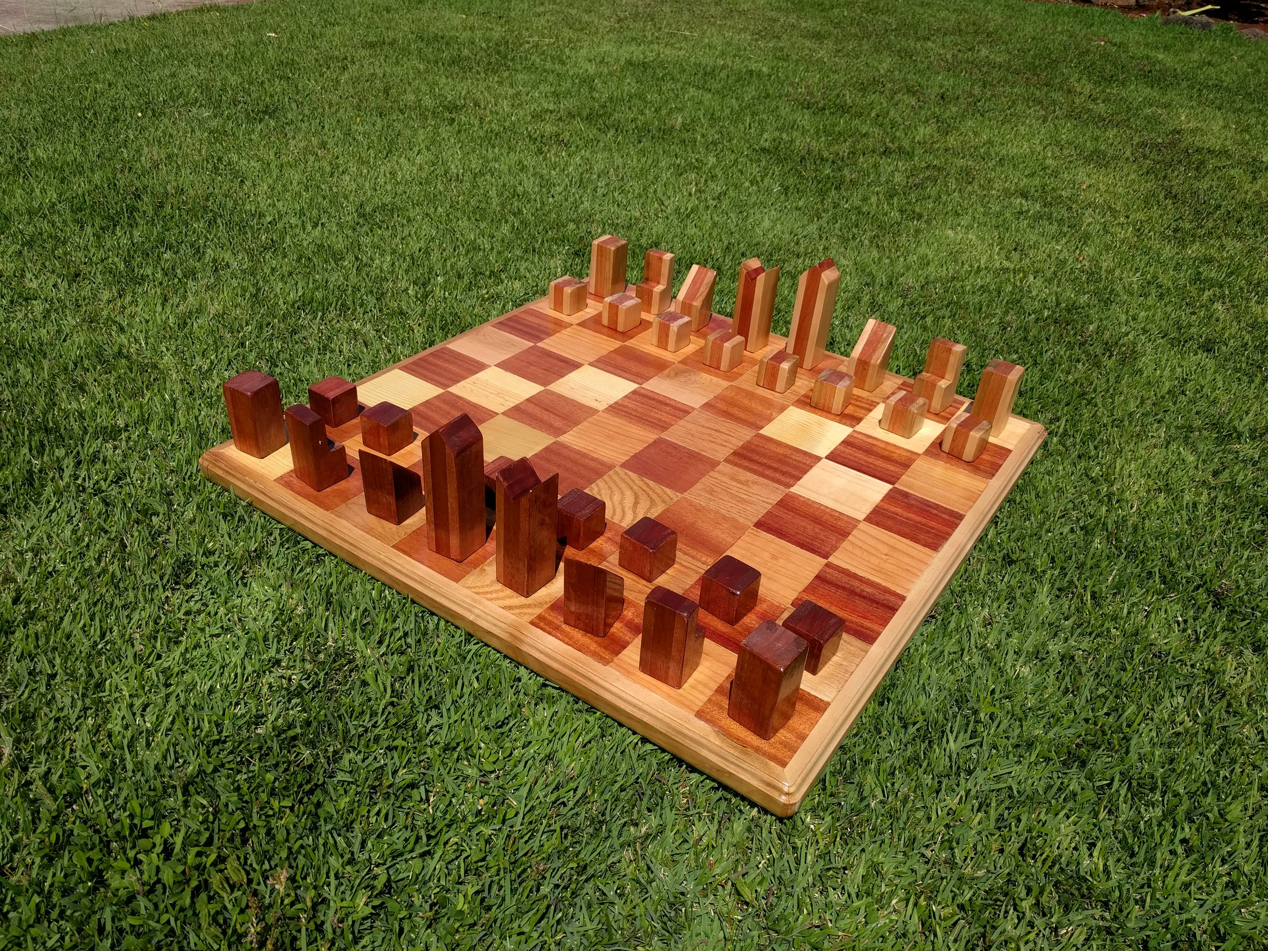 Chess - Truly the thinking mans Great Big Game. Each piece is carved out of Mahogany and Maple. The pieces are in the shape of the action the piece can take.