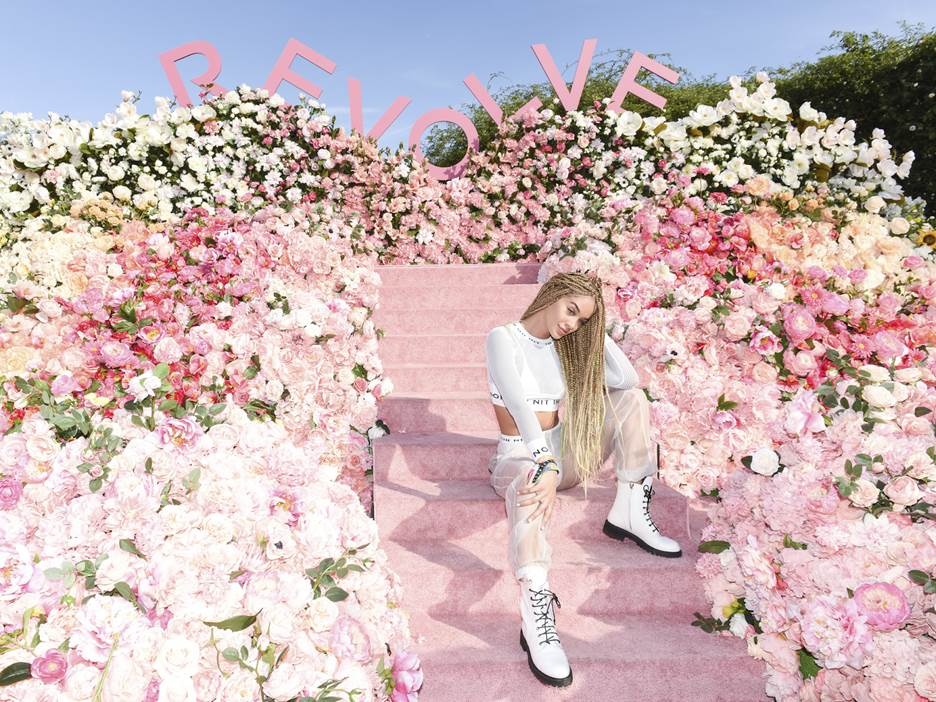Jasmine Sanders poses at the #REVOLVEfestival flower wall