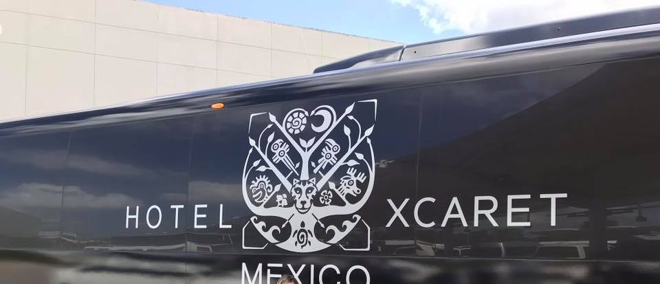 Logo on the airport shuttle for Hotel Xcaret. Round trip transfers to Cancun International Airport are included in your stay.