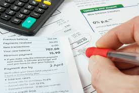 financial-documents-on-desk-with-person-hand-writing-on-them-and-a-calcualtor.jpg