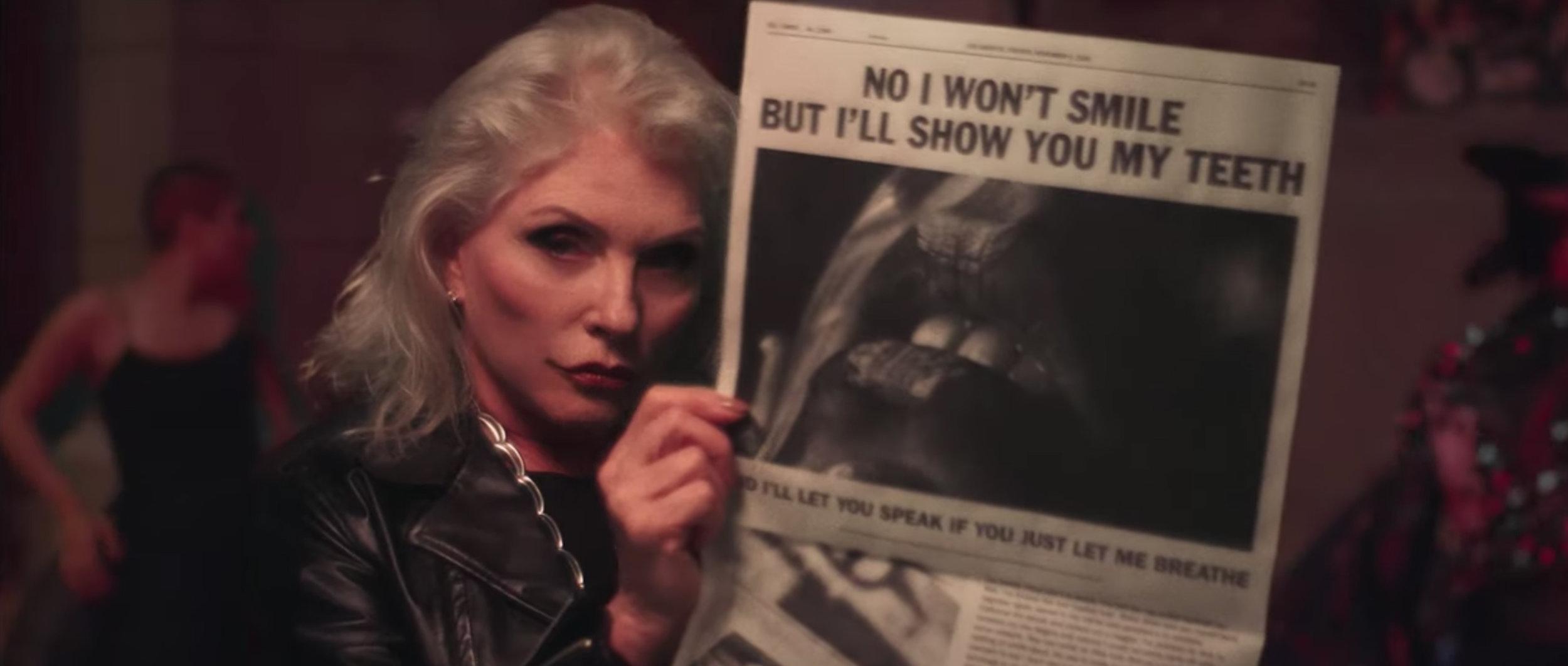 Debbie Harry of Blondie holding the newspaper.