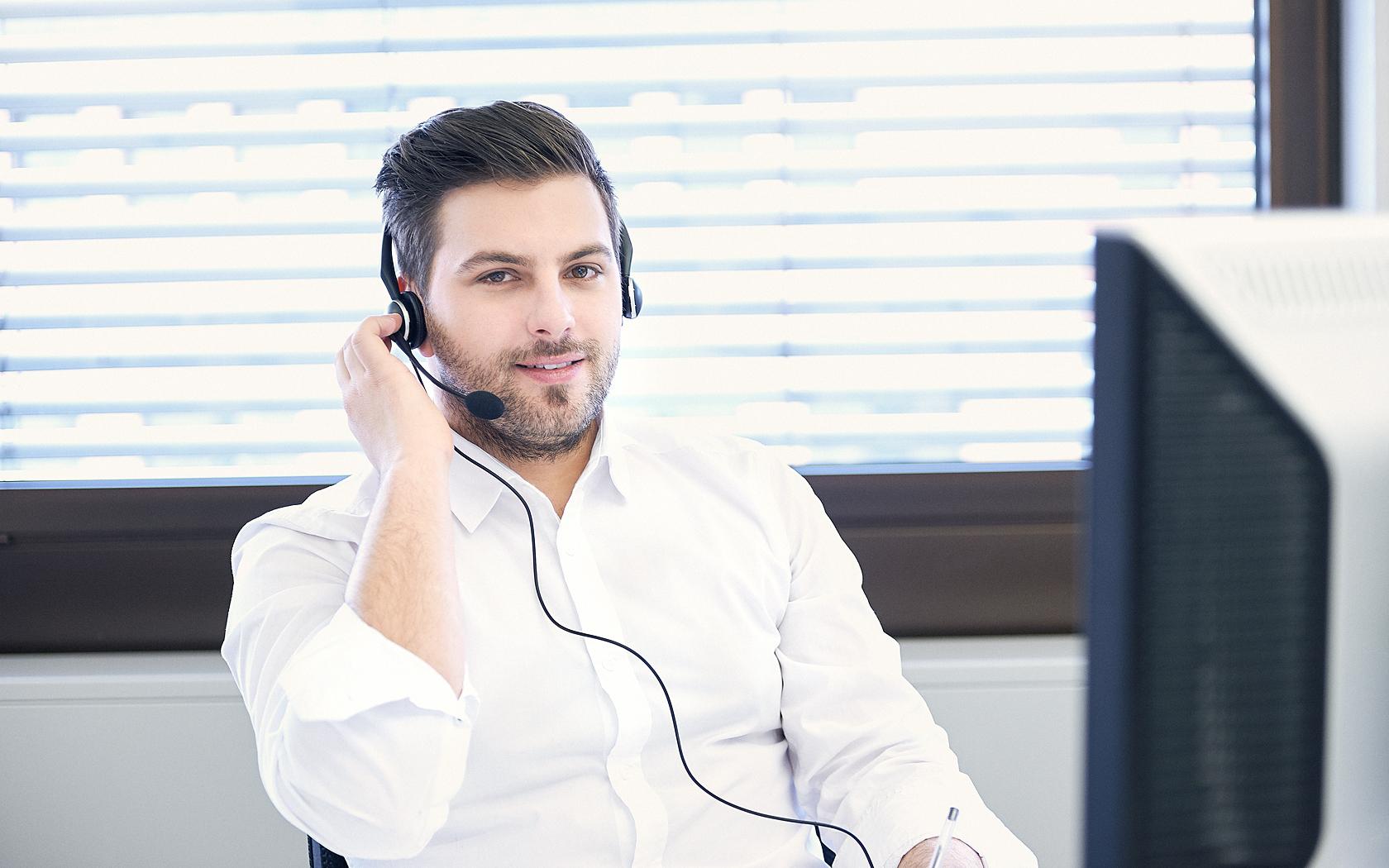 Callcenteragent mit Dreitagebart weissem Hemd und Headset, sitzt am Computer und blickt direkt in die Kamera