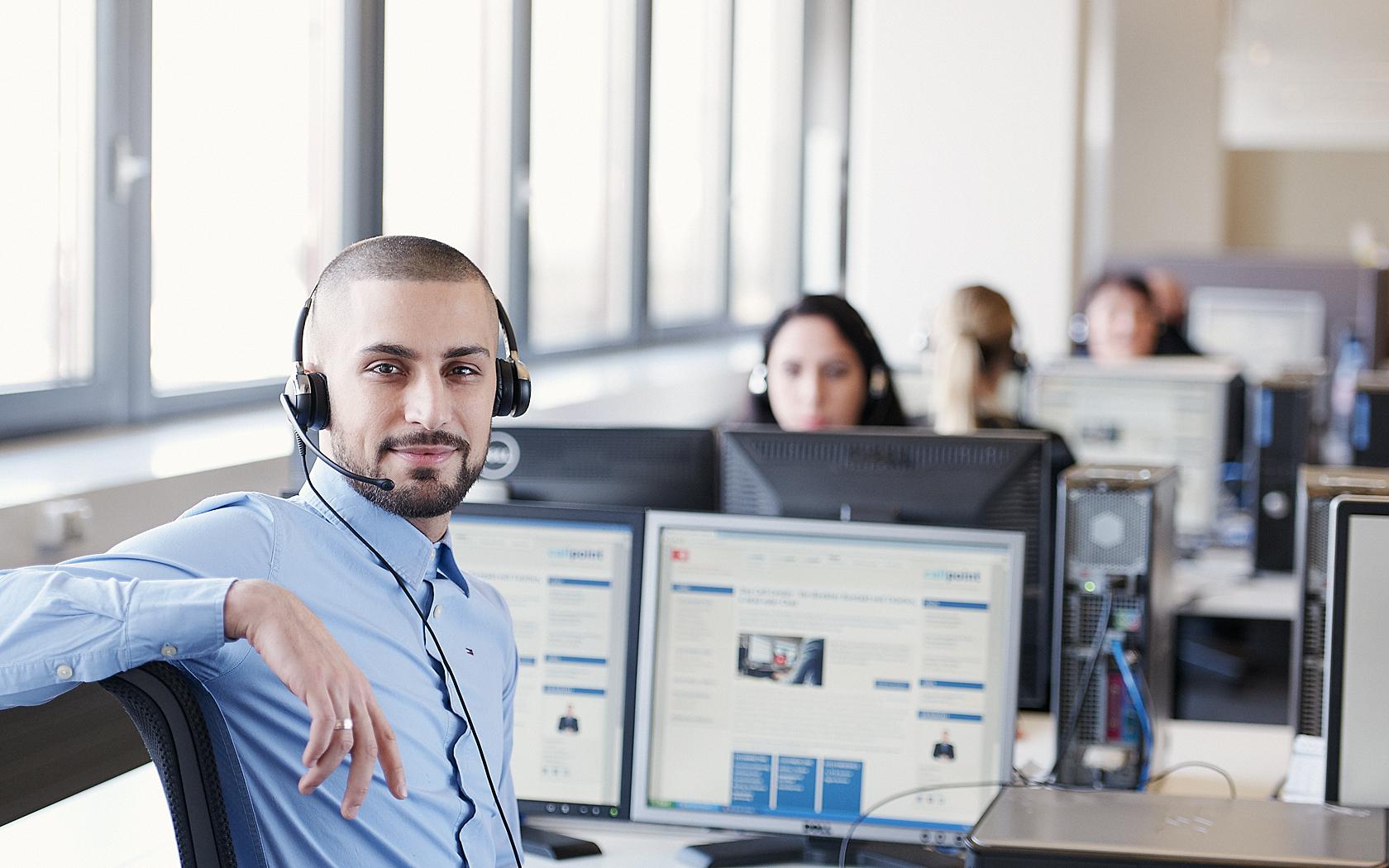 Callcenter Mitarbeiter mit Dreitagebart, blauem Hemd und Headset, blickt direkt in die Kamera,