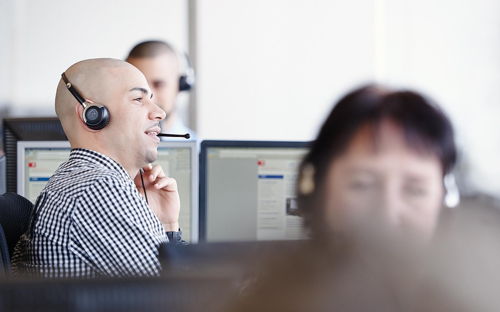 Callcenter Mitarbeiter- und Mitarbeiterinnen mit Headset an heller Fensterfront mit Tagelcht