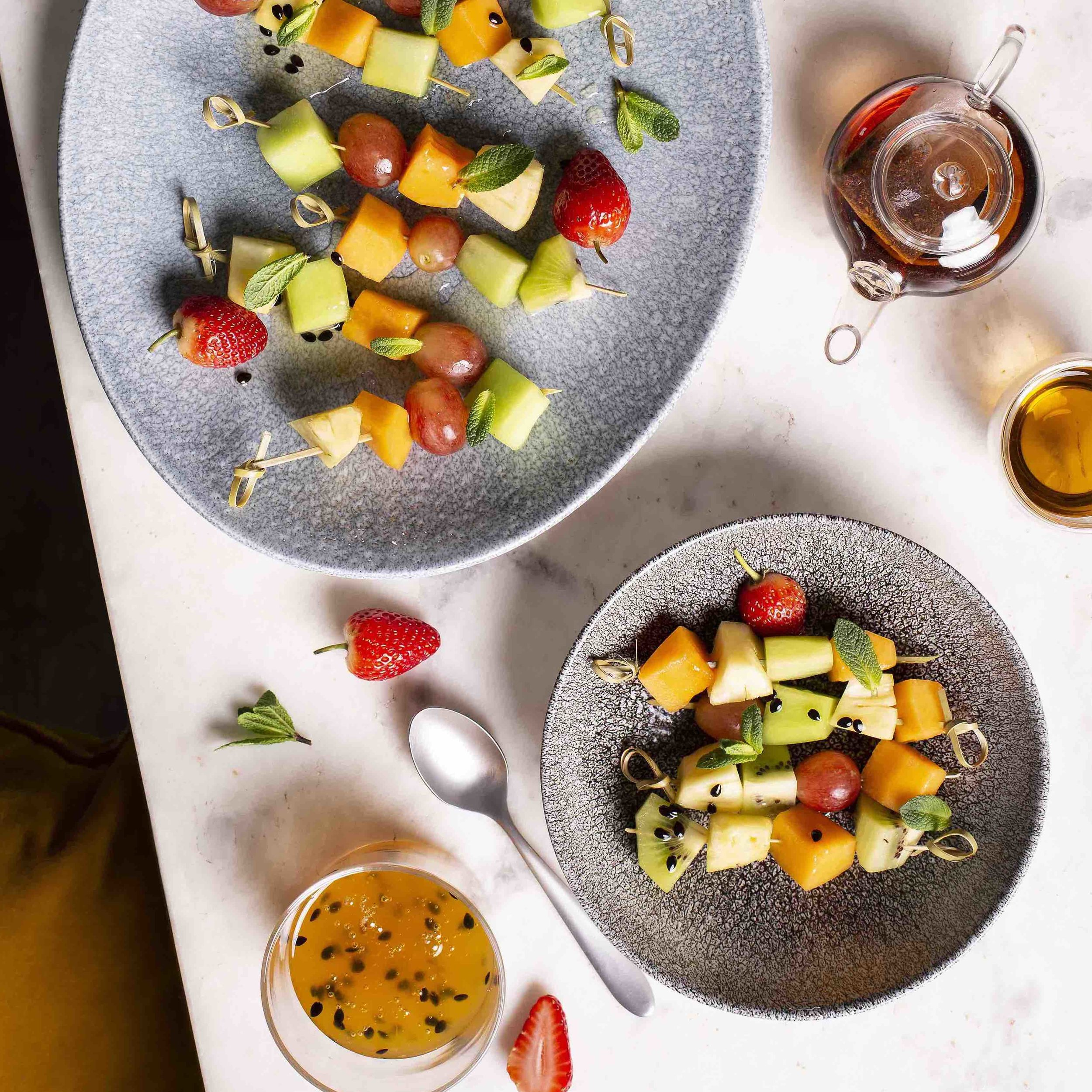 Seasonal Fruit KebabsR 440 – - Seasonal fruit kebabs with edible flowers and passion fruit drizzle