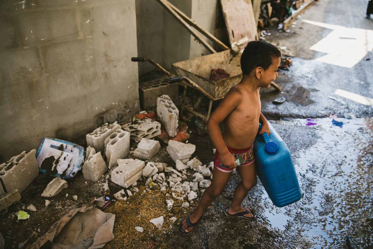 A small child carrying a water can down an alley inShatila.