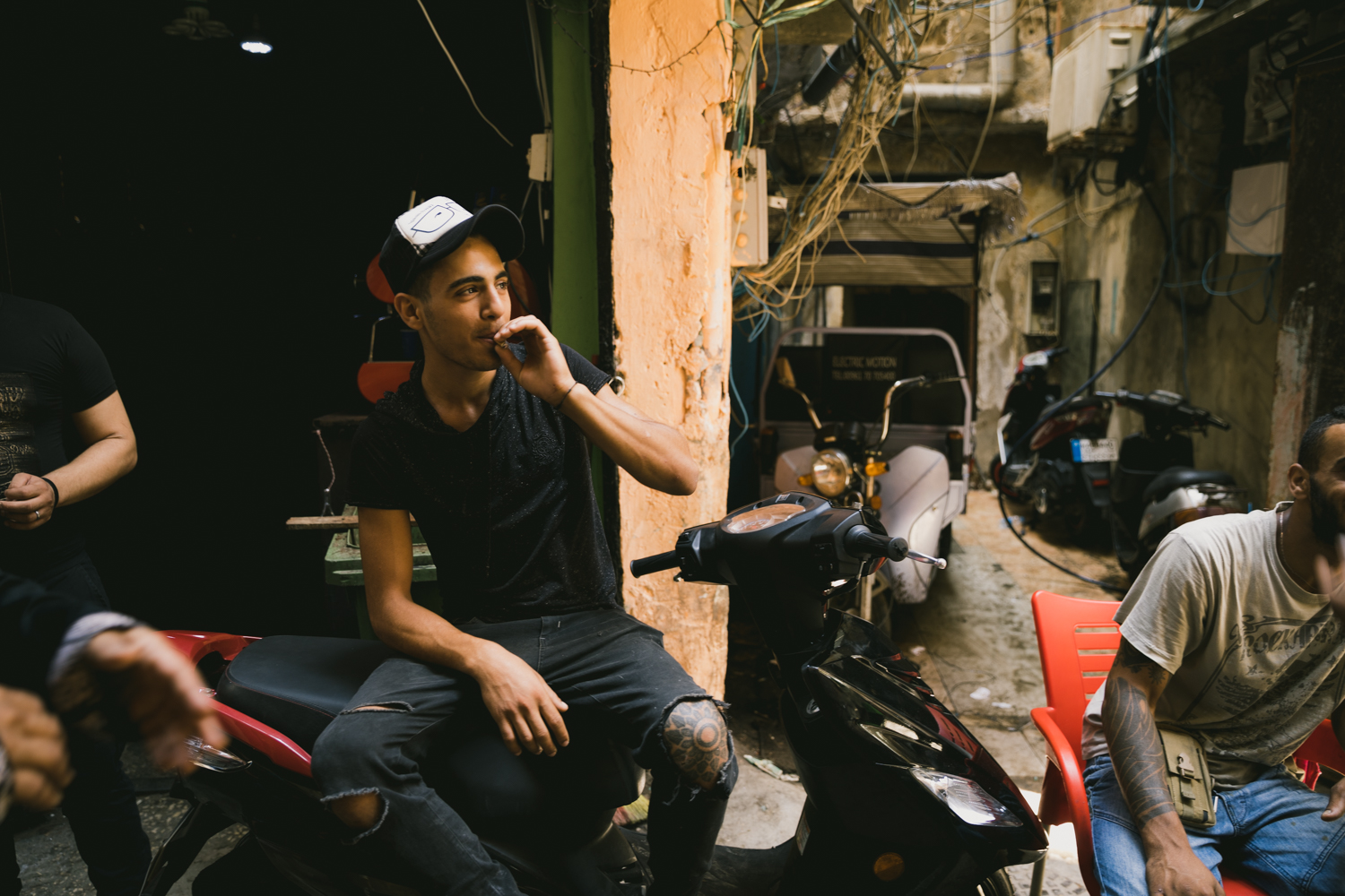A young Palestinian man smokes a cigarette while hanging with friends during the middle of the day. Due to complications with the legal and social status of Palestinians in Lebanon, most people in the camps struggle to find work, and thus spend good portions of the day in the alleys and streets as their homes are often inhabitable in the midday heat.