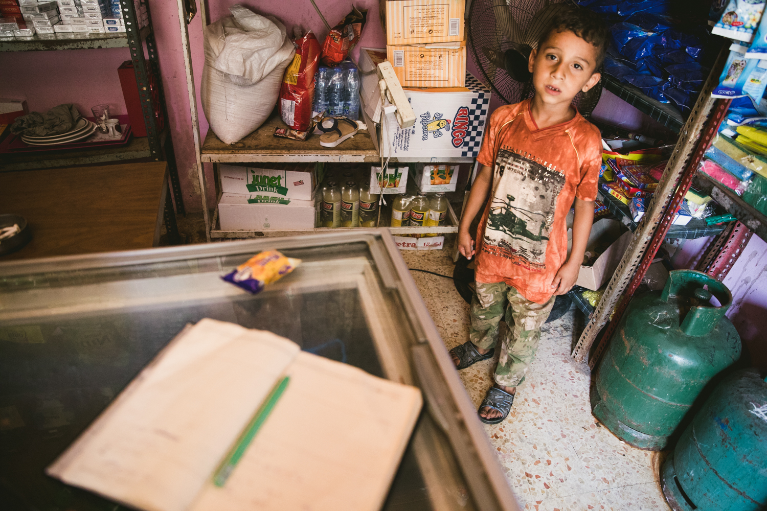 A young Palestinian boy inside a small shop.