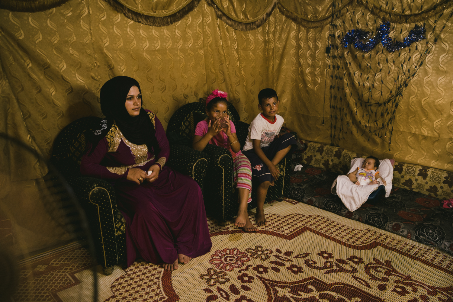 A young mother sits with her children in their tent inside the Sad Nail camp in the Bekaa Valley.