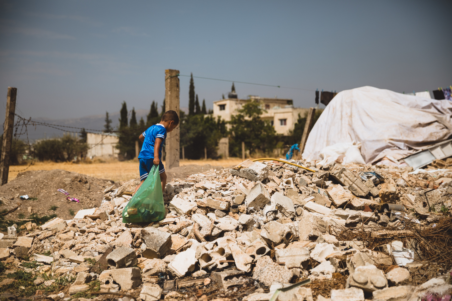 A young child drags trash across a rubble pile in a small camp in the Bekaa Valley.