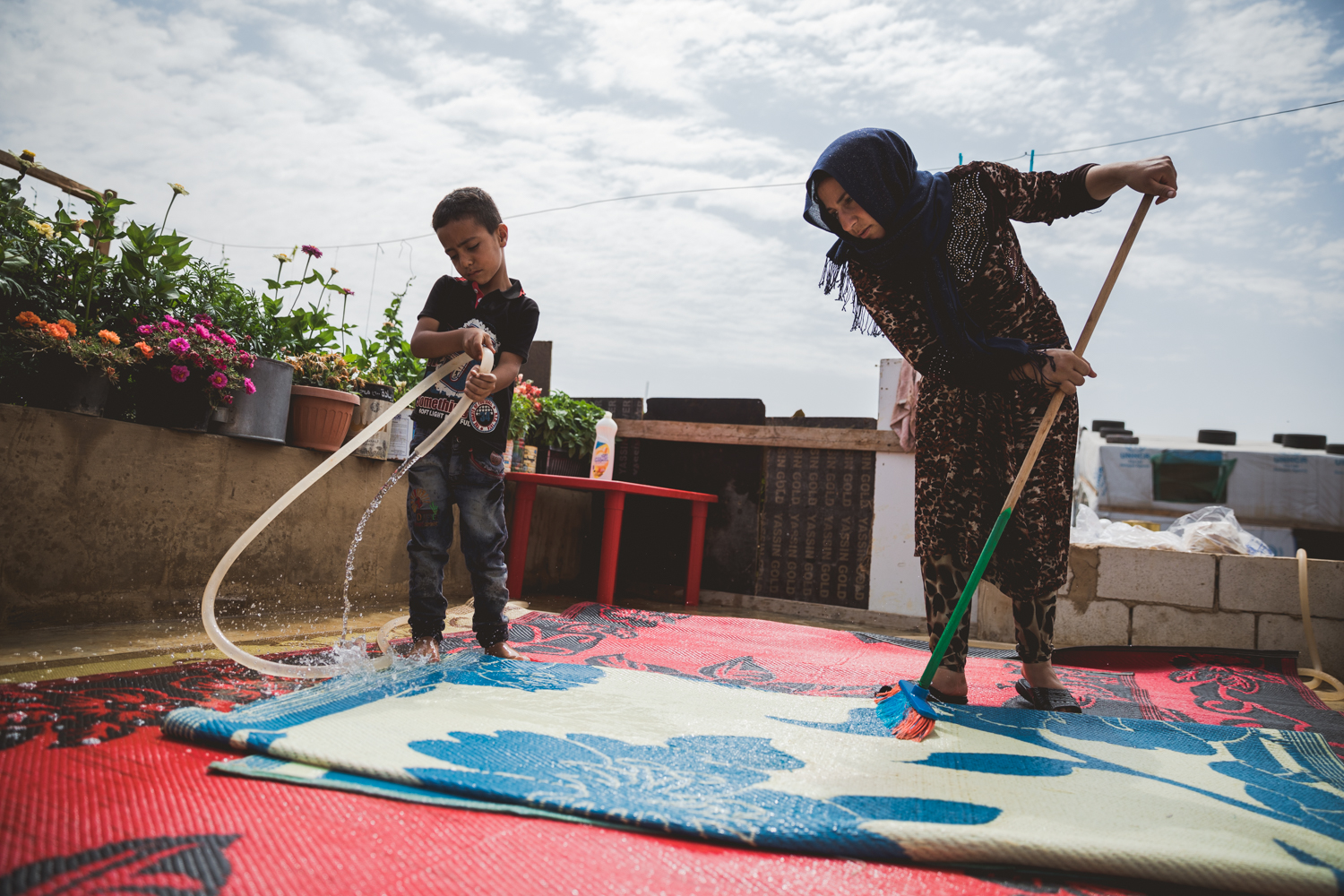 A young boy and his mother cleaning the rugs of their tent.