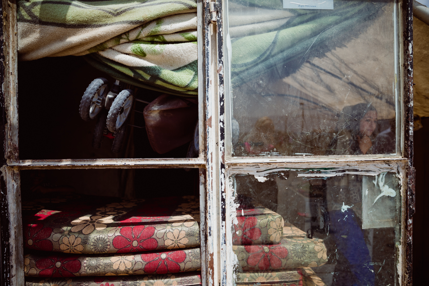 An old window leans against the outside of a tent housing a refugee family.