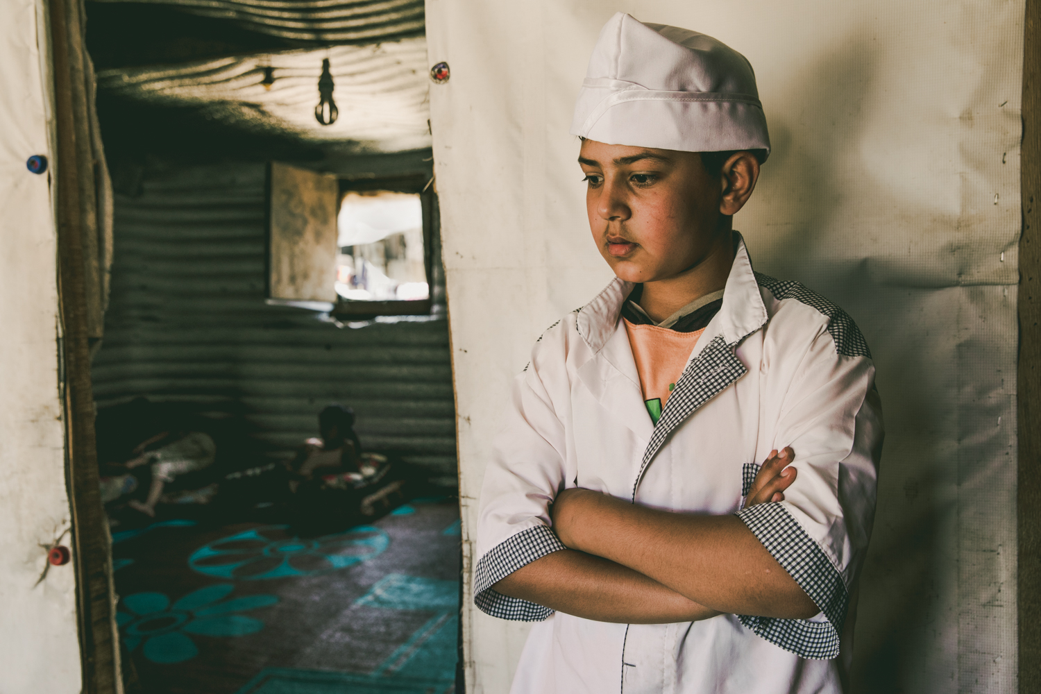A young boy returning from his work shift stands outside the door to his family's tent.