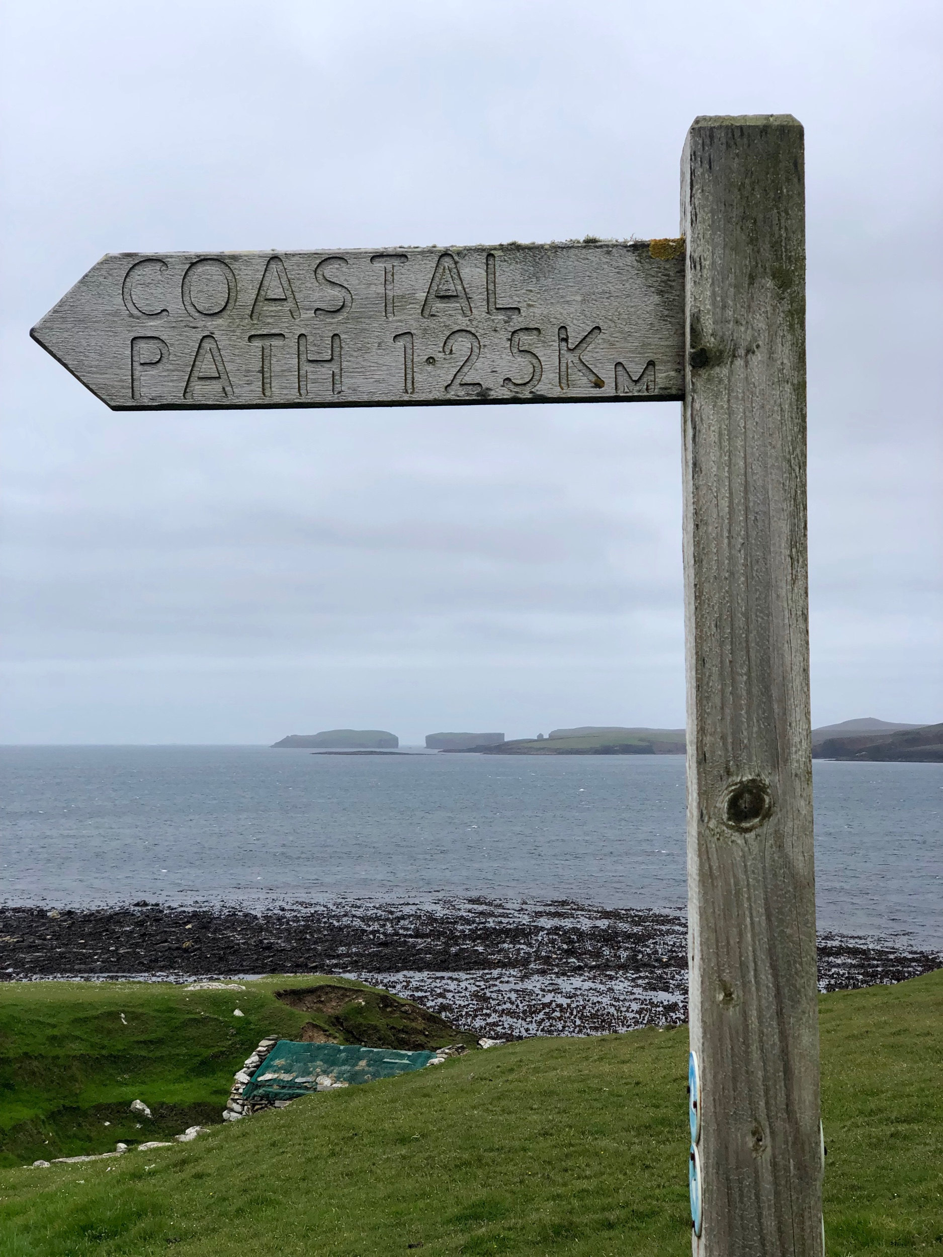The coastal path at Sandness with a view of Magnus Bay and the west end of Papa Stour island.