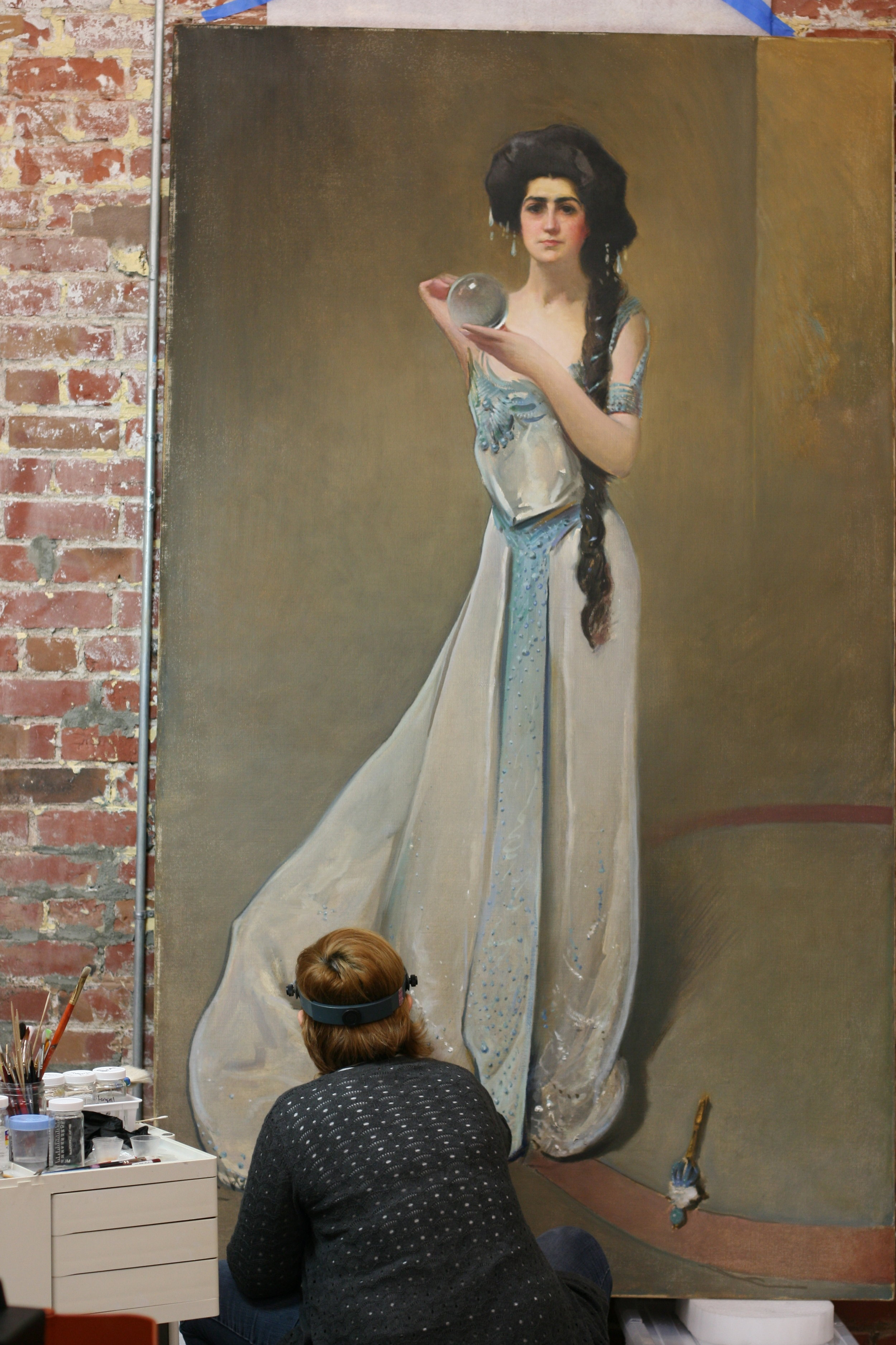 """Stephanie treats a large 19th century portrait titled """"Phoebe of the Titans, Portrait of Katherine Mackay"""" by John White Alexander. from the W. M. Kick Earth Science and Mineral Engineering Museum, Nevada."""