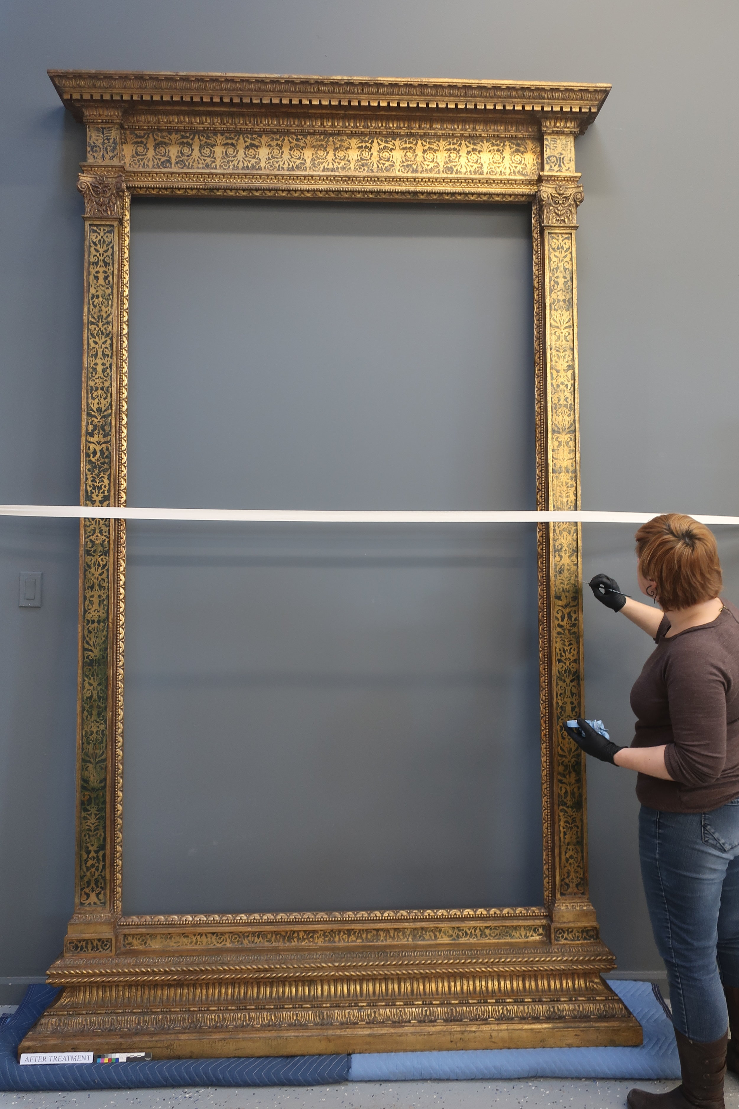 High Ceilings and walls painted gray provide a neutral background for photographing large pieces. Pictured here is the ornate gilded frame that accompanied the painting to the left.