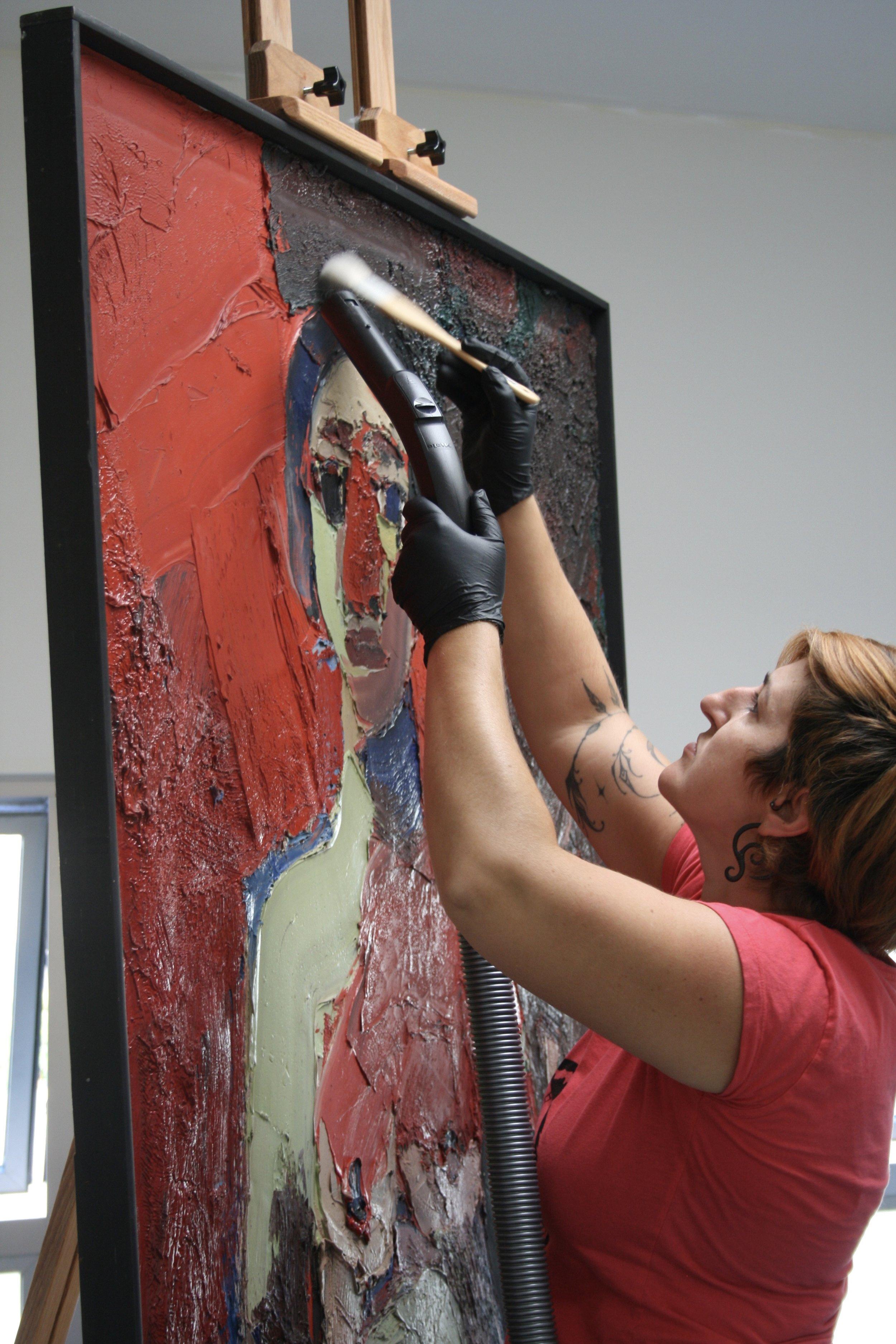 Stephanie Limoges, Senior Paintings Conservator, vacuuming a Joan Brown painting