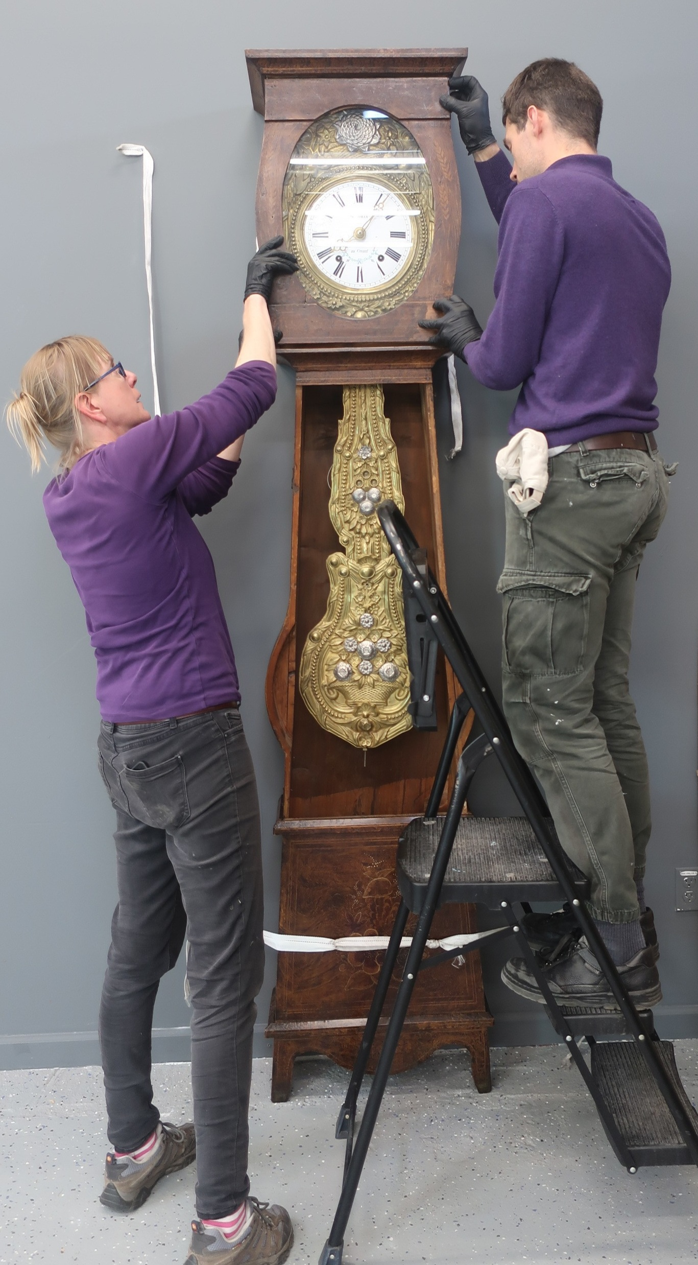 Team works together on an antique handmade grandfather clock