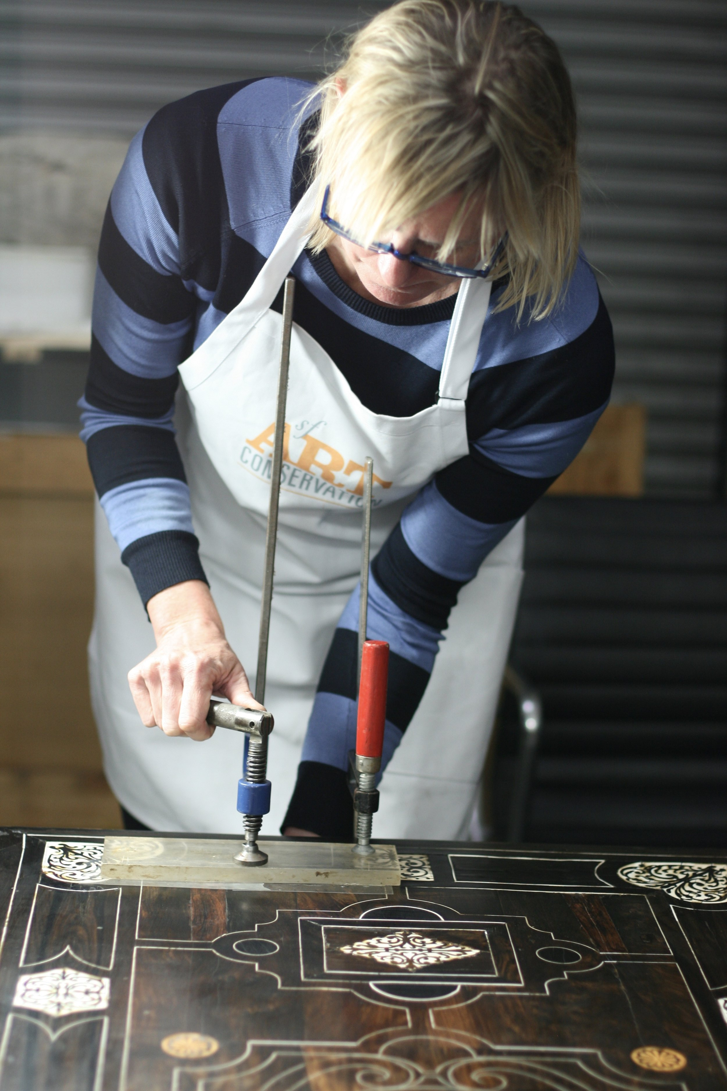 Sarah Johnson, a specialist in furniture, repairs inlay