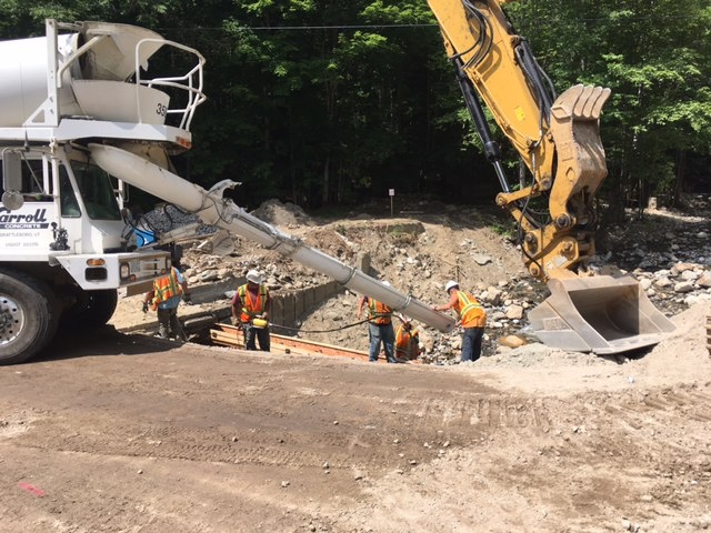 DOT workers pour concrete on Cardigan Mountain Road below New Colony. State trucks are able to get across the brook, and two-way public traffic will be allowed soon.