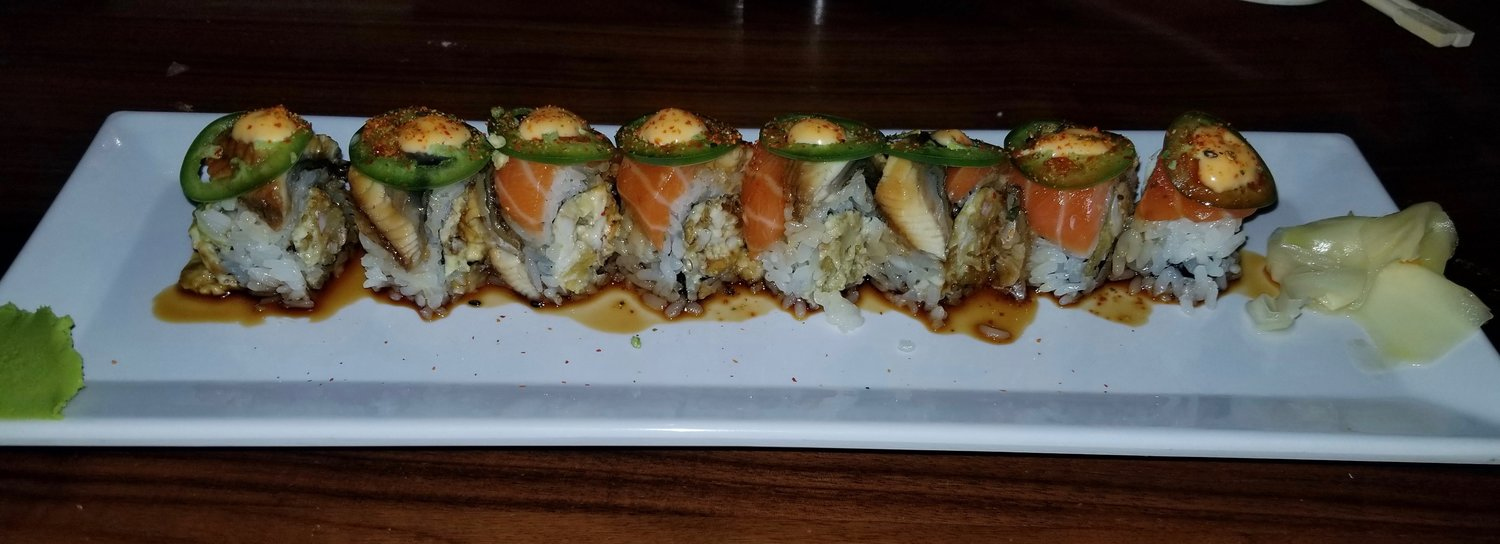 The Tsunami Roll- a spicy soft shell crab roll topped with salmon, eel and jalapeño.