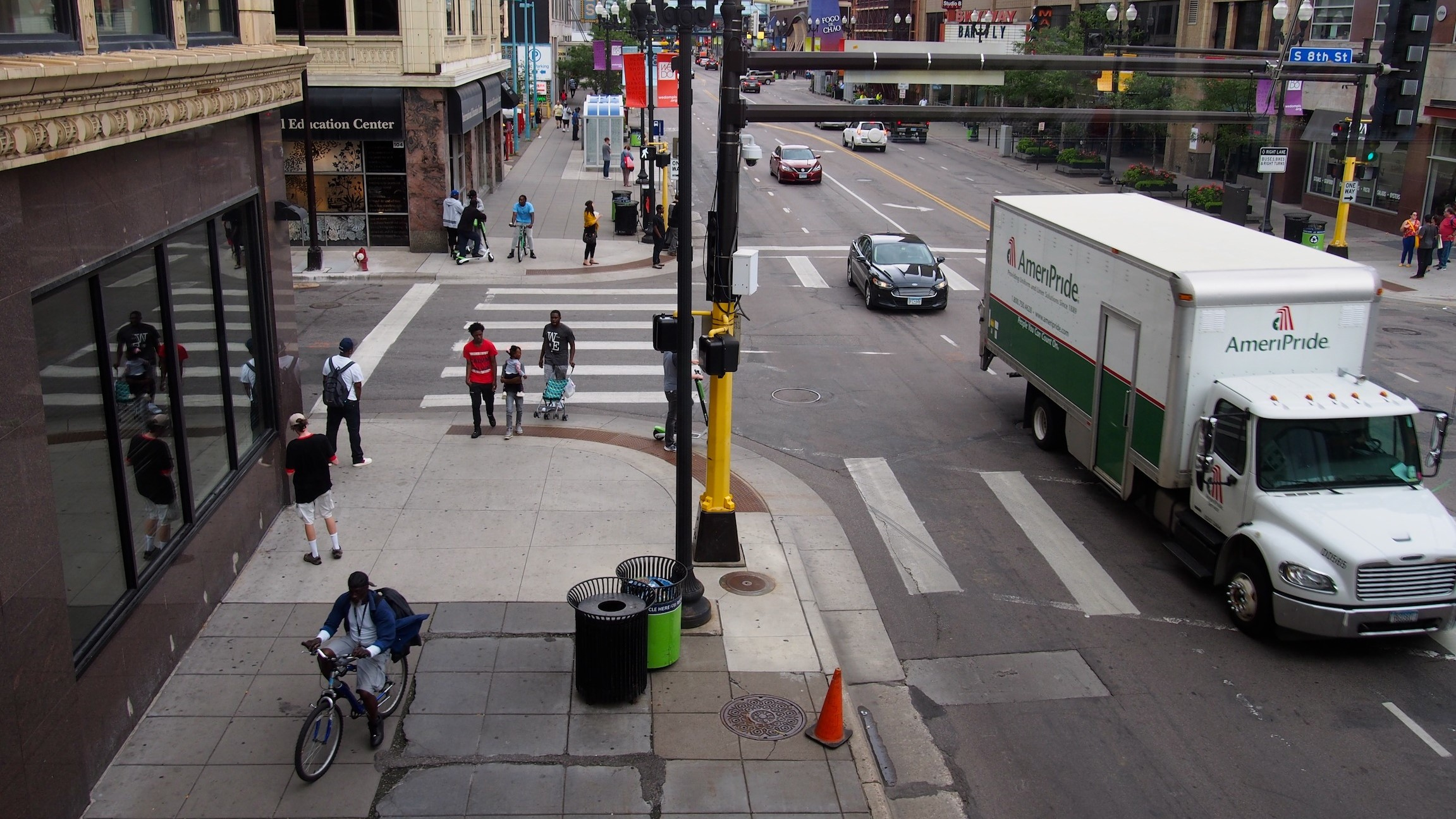 In Downtown Minneapolis, people are moving, standing, scooting, biking, driving, and waiting for transit on a 5-lane road that crosses South 8th Street.