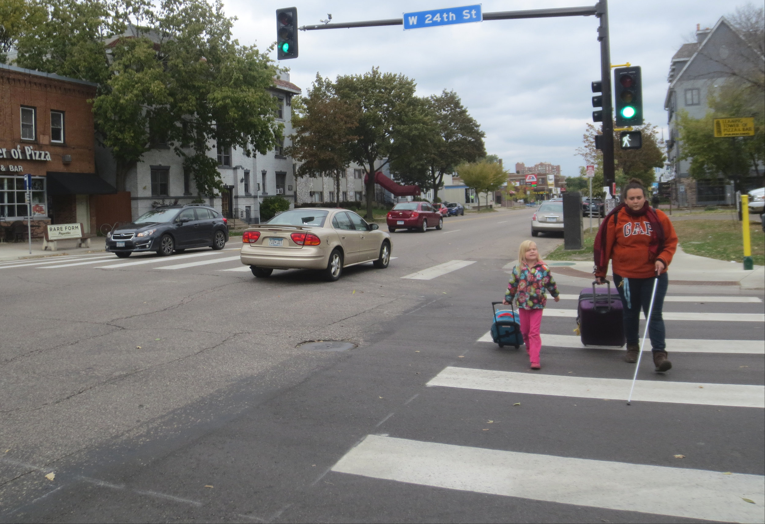 A woman with a white support cane walks with a small girl in a crosswalk along West 24th Street. Both are pulling rolling suitcases and are crossing with the right of way while motor vehicle traffic travels in the road next to them.
