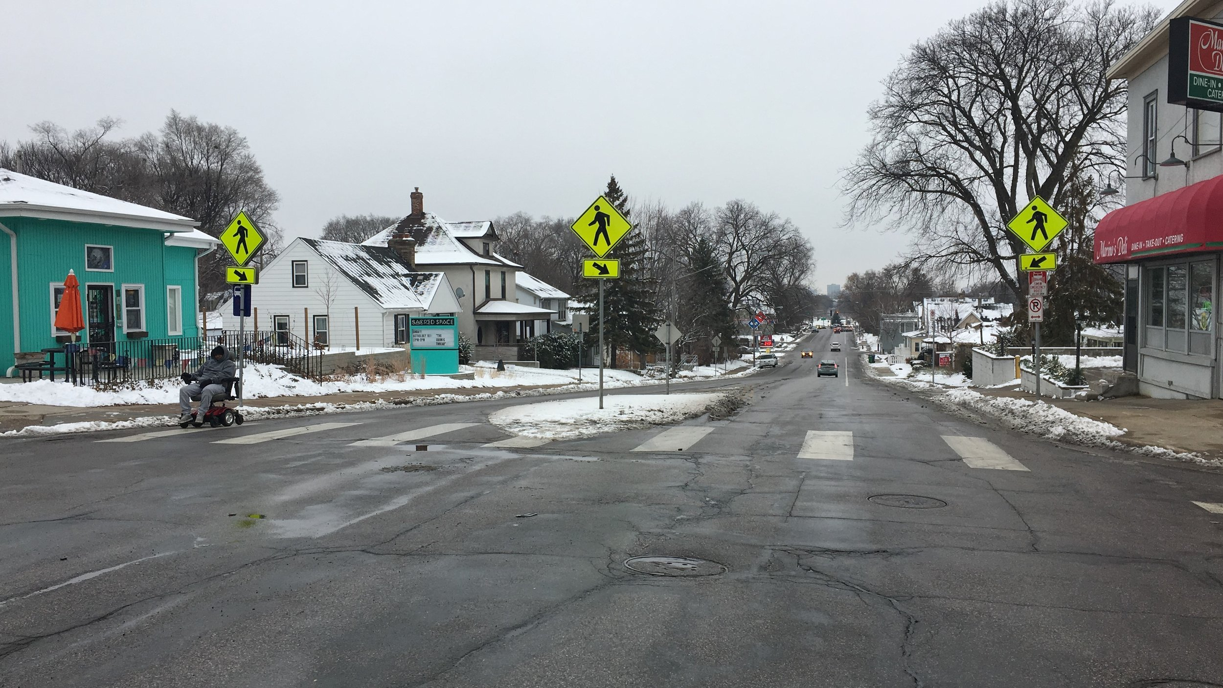 A suburban streetscape in winter, where a black man in a motorized wheelchair rolls in the street to avoid piles of snow around driveways and sidewalks. No cars are coming.