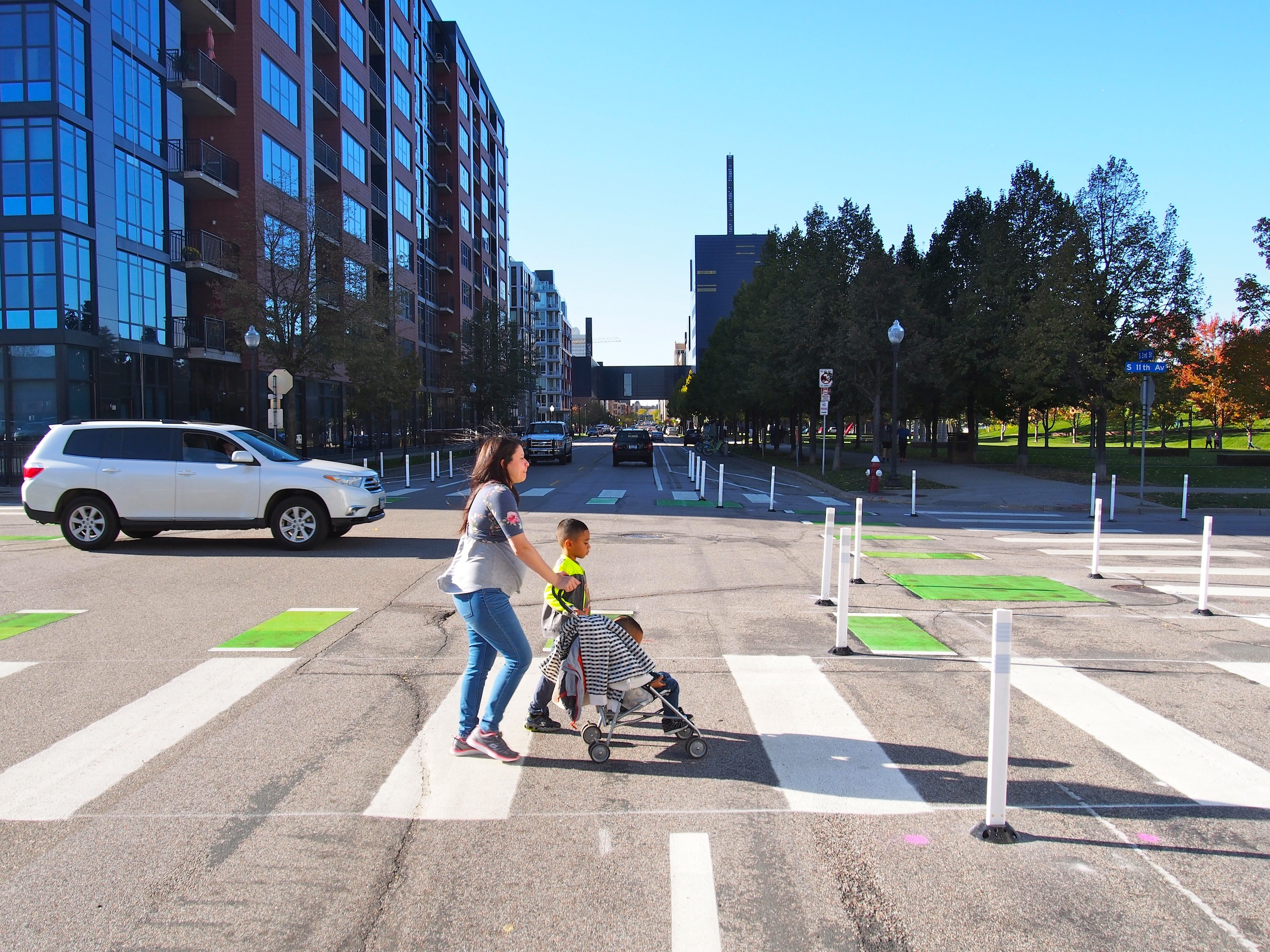 A woman and her two children cross a street with bike lanes on either side. It features designs that slow cars turning right and left, to ensure shorter crossing distances.