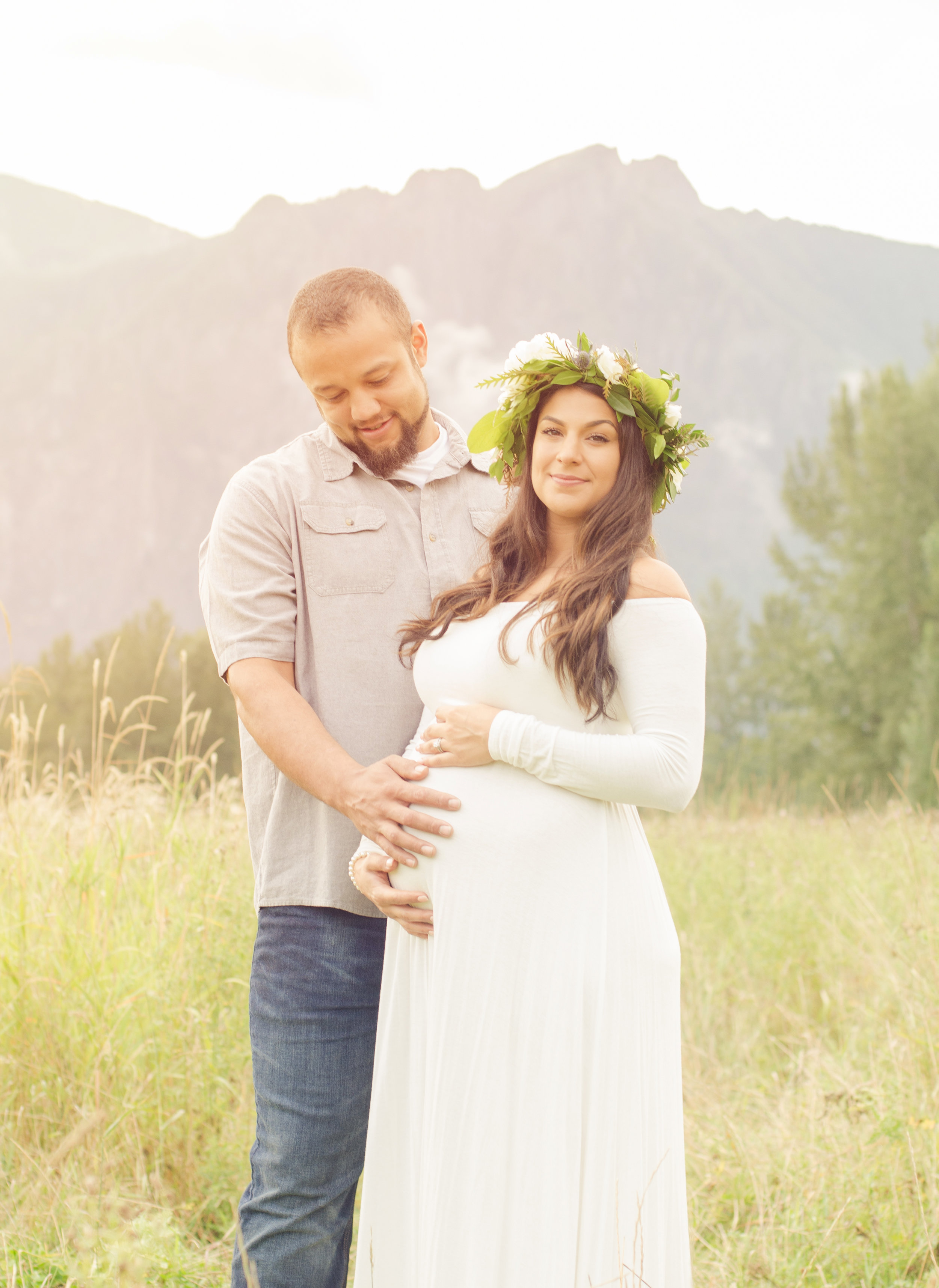 New mom confidently looking at photographer while dad embraces belly