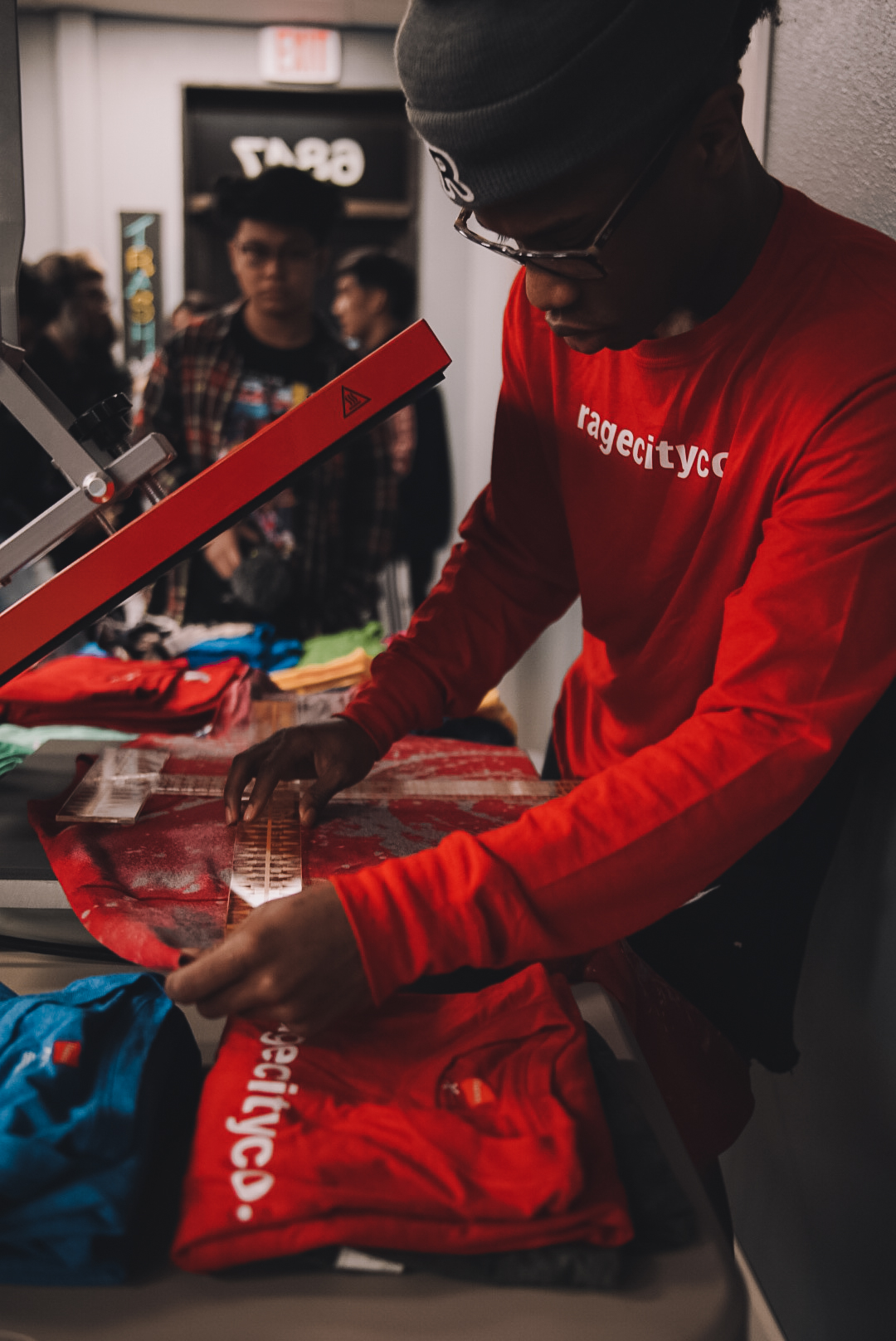 Deven Jackson prints T-shirts at an event in Anchorage. Jackson, along with Qyntyn Pilcher, hopes to expand the company throughout the city. Photo credit: Rage City Company