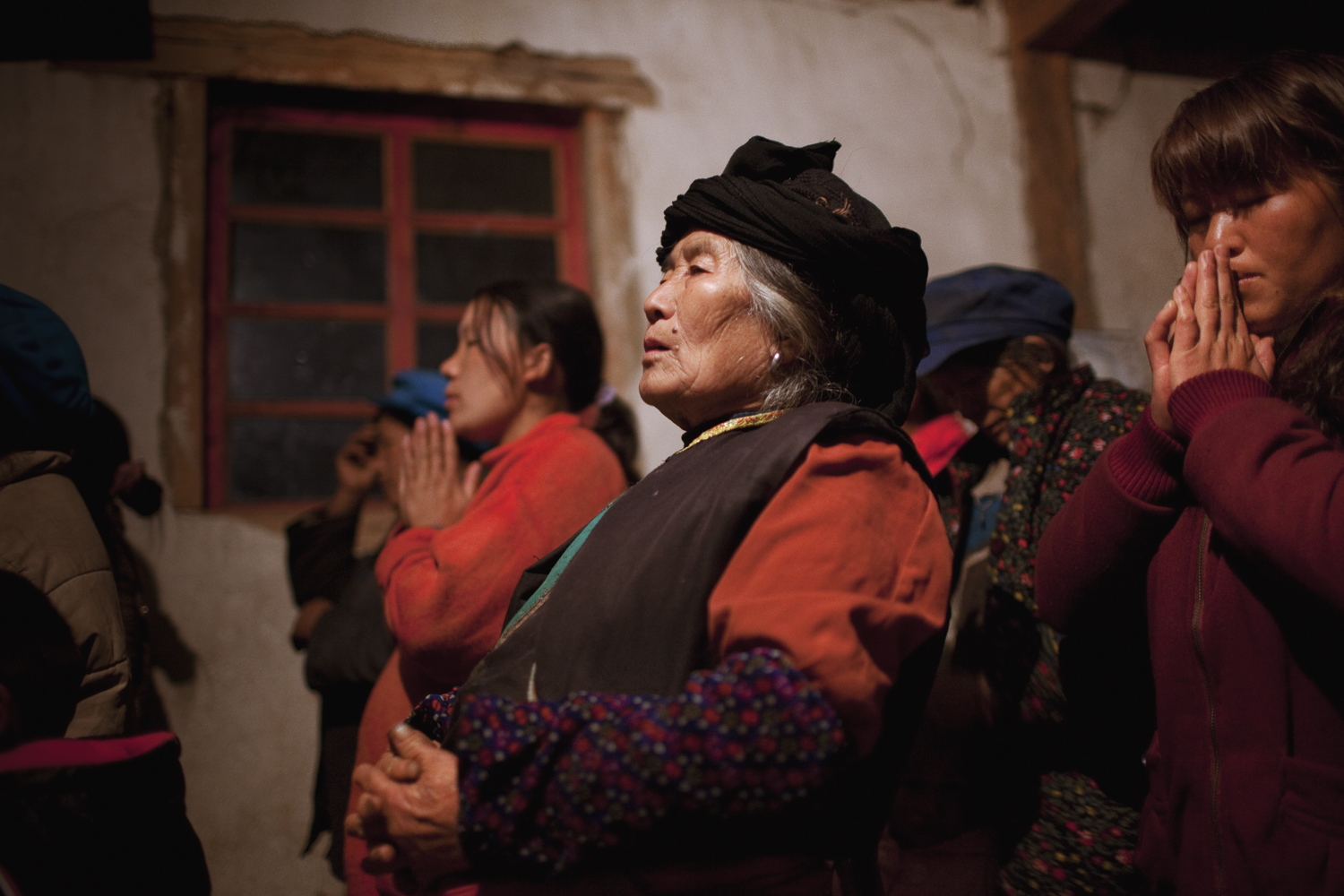 Qiunatong Village, Yunnan. Most of the minority groups converted to Christianity a hundred years ago when missionaries crossed over from Burma. Villagers gather for a late night mass on New Year's Eve.