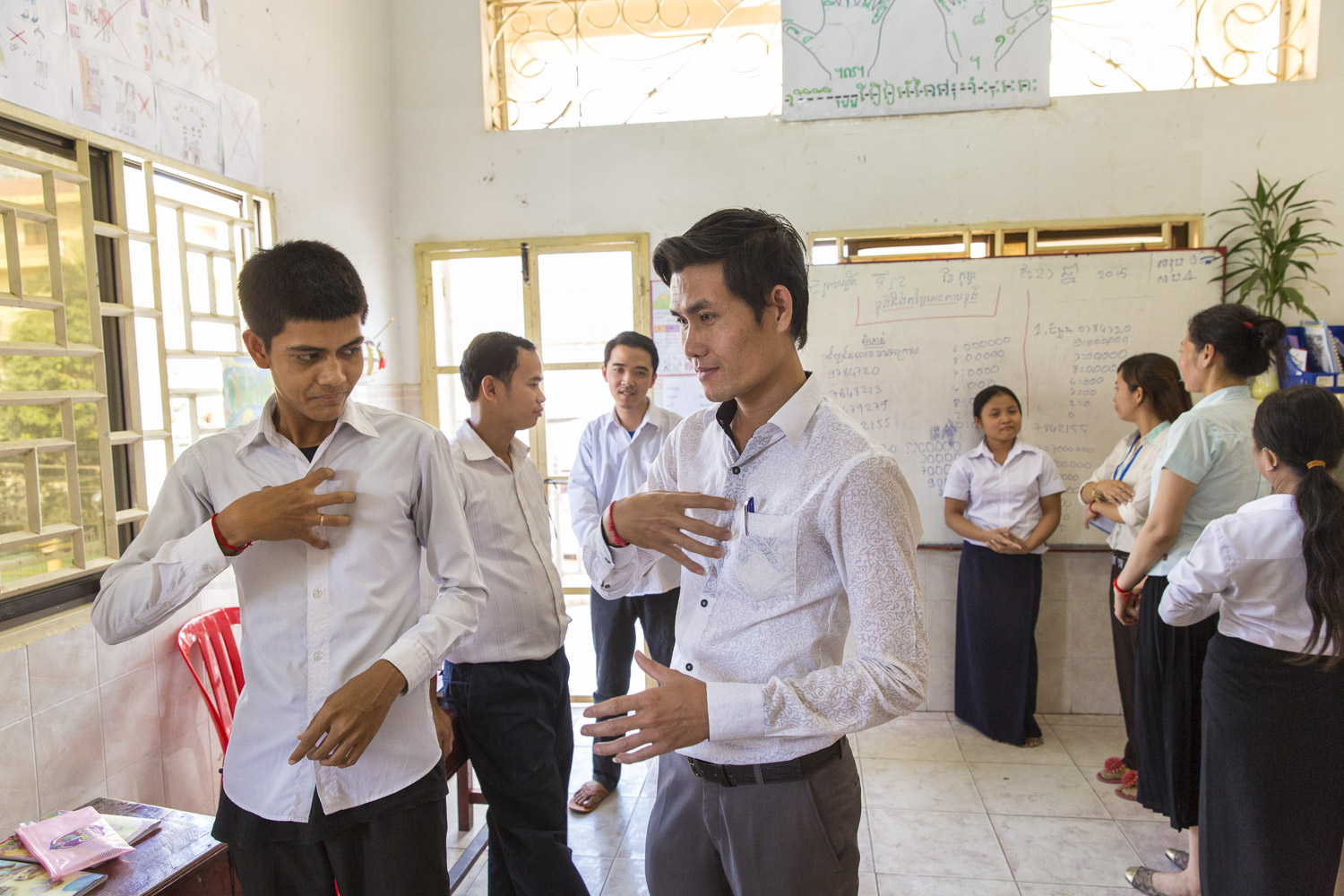 Sopor Lay (middle) a graduate of DDP's program is now a teacher at their Phnom Penh center.