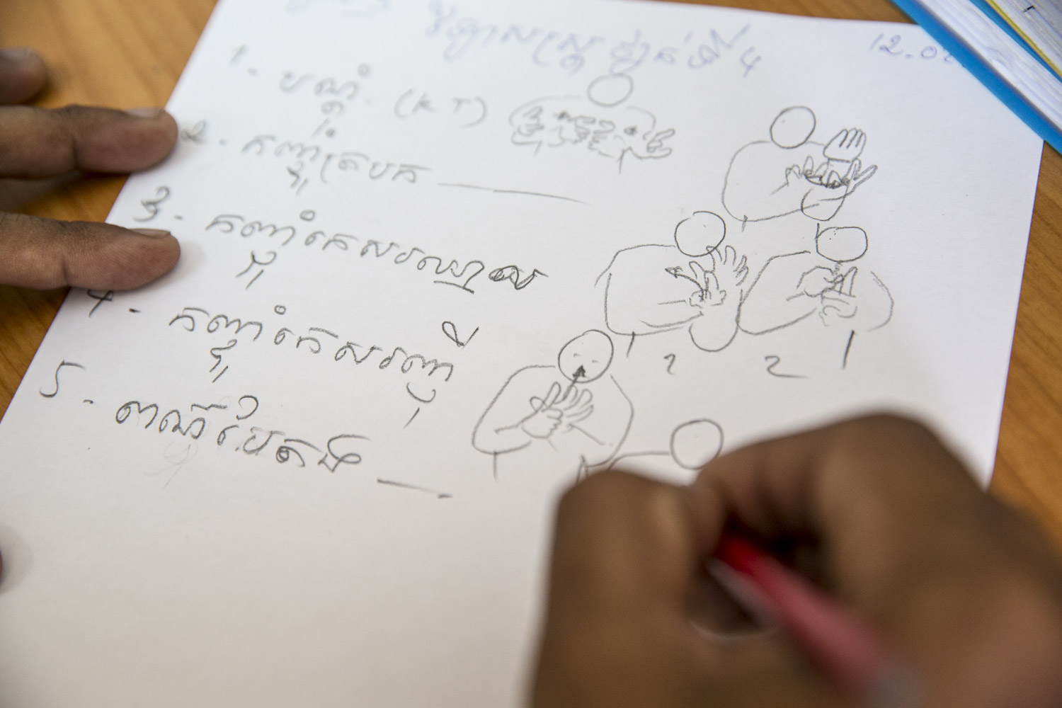 Sam Ath Heang's hands at a language creation session where Cambodian Sign Langauge is being created on a daily basis. Once there is agreement between the participants ,Sam Ath draws the gestures on paper. Later the drawing will be converted to a digital illustration.