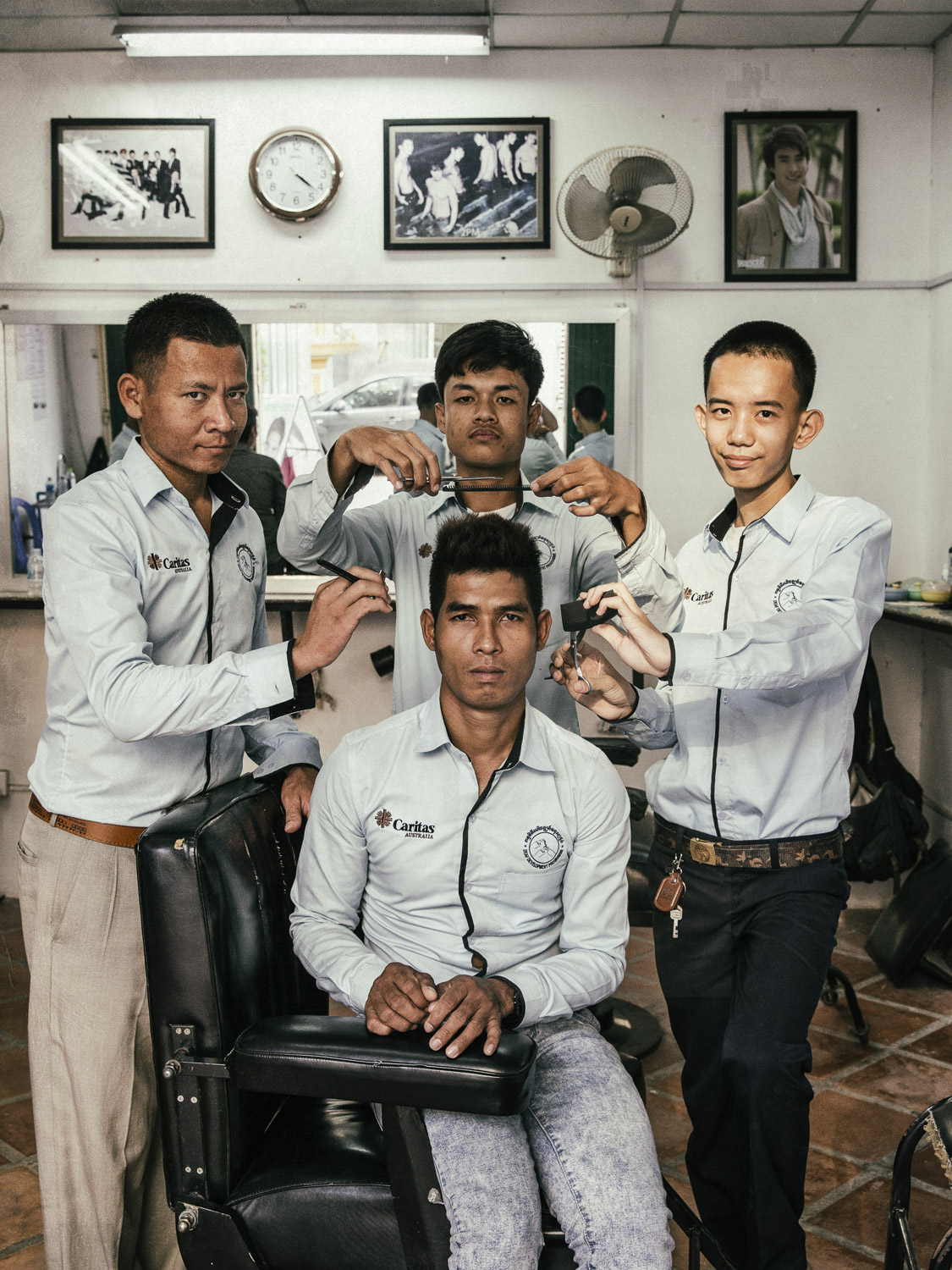 Deaf students at the barber vocational school located in the bottom floor of DDP's Phnom Penh center. Local people often use the services of the barbers at the training center which doubles as a barbershop.