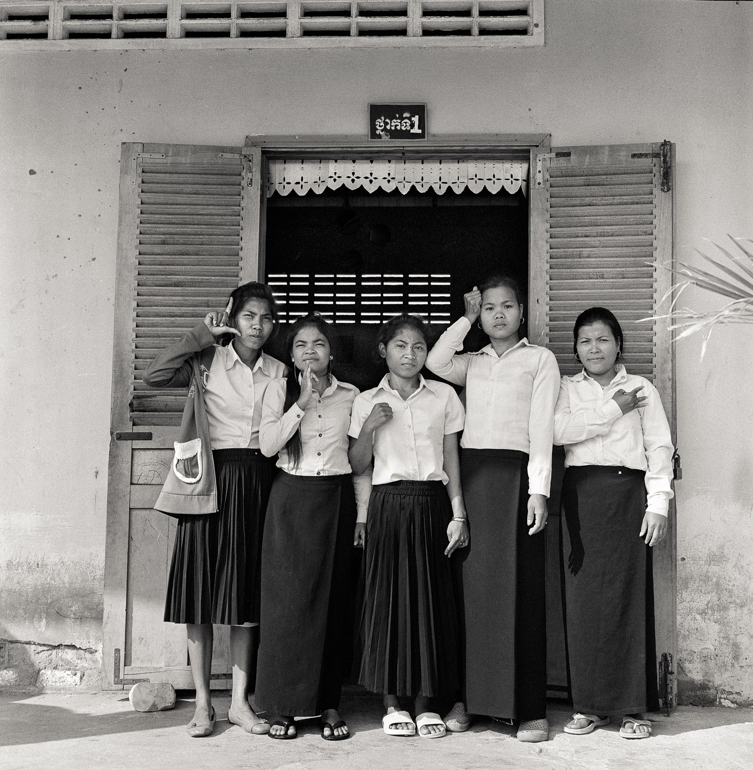 Basic Education students in Kampot, Cambodia.  Each student is showing their name sign in front of their classroom.