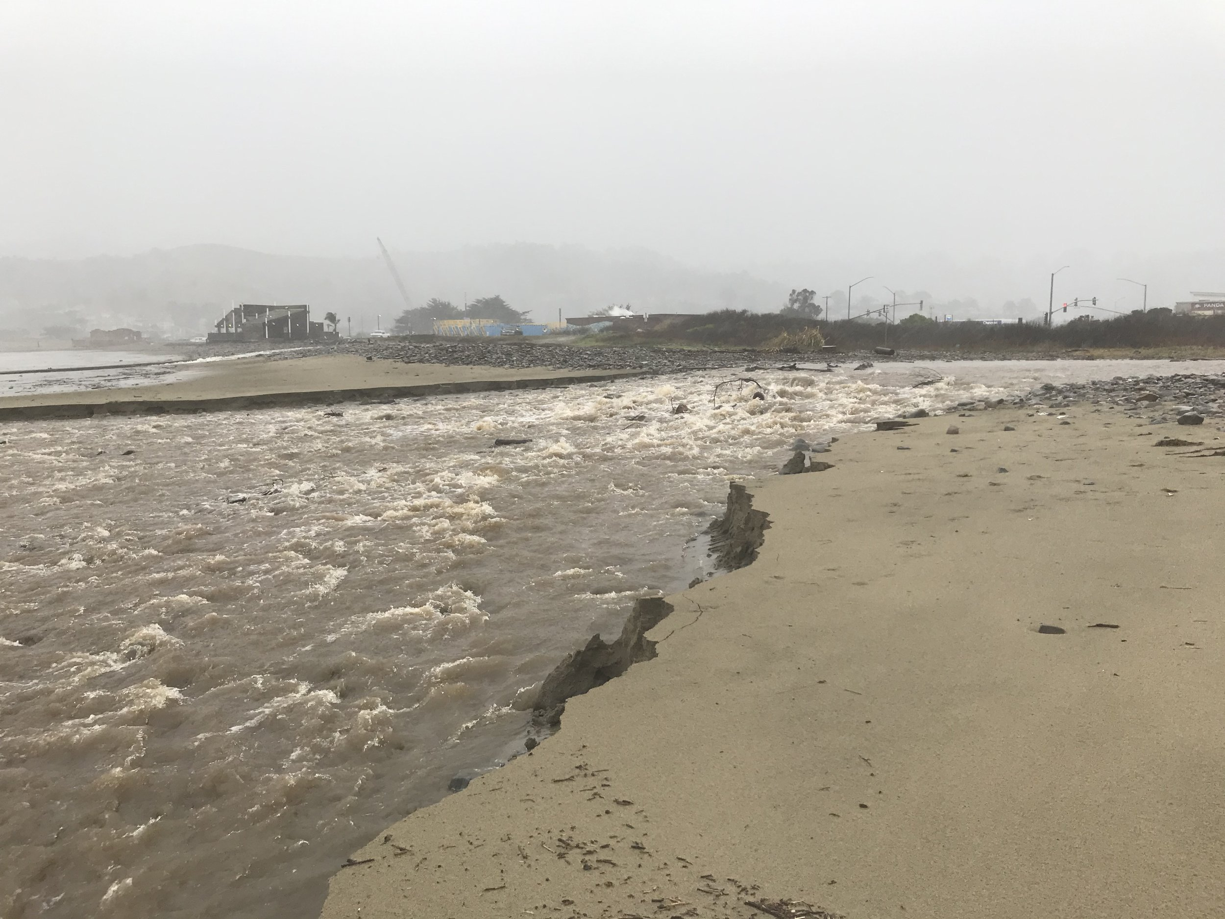 San Pedro Creek entering crossing Linda Mar Beach (foreground). Pacifica's raw sewage crossing the beach (background, in front of Taco Bell).
