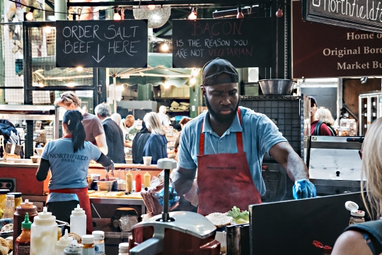 Staff cooking at market stand