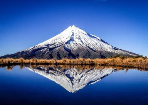 Taranaki Mountain in New Zealand reflected in serene lake