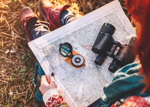 Woman on hike looking at map with compass on it for direction