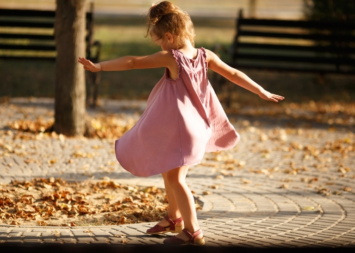 Little girl dancing in the park