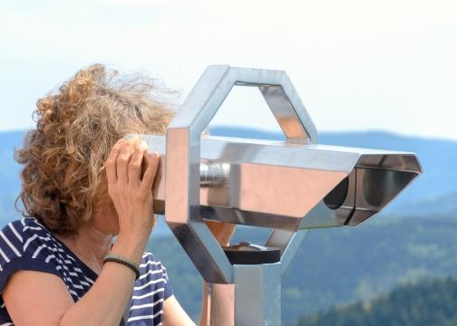 Woman looking through a binocular telescope.jpg