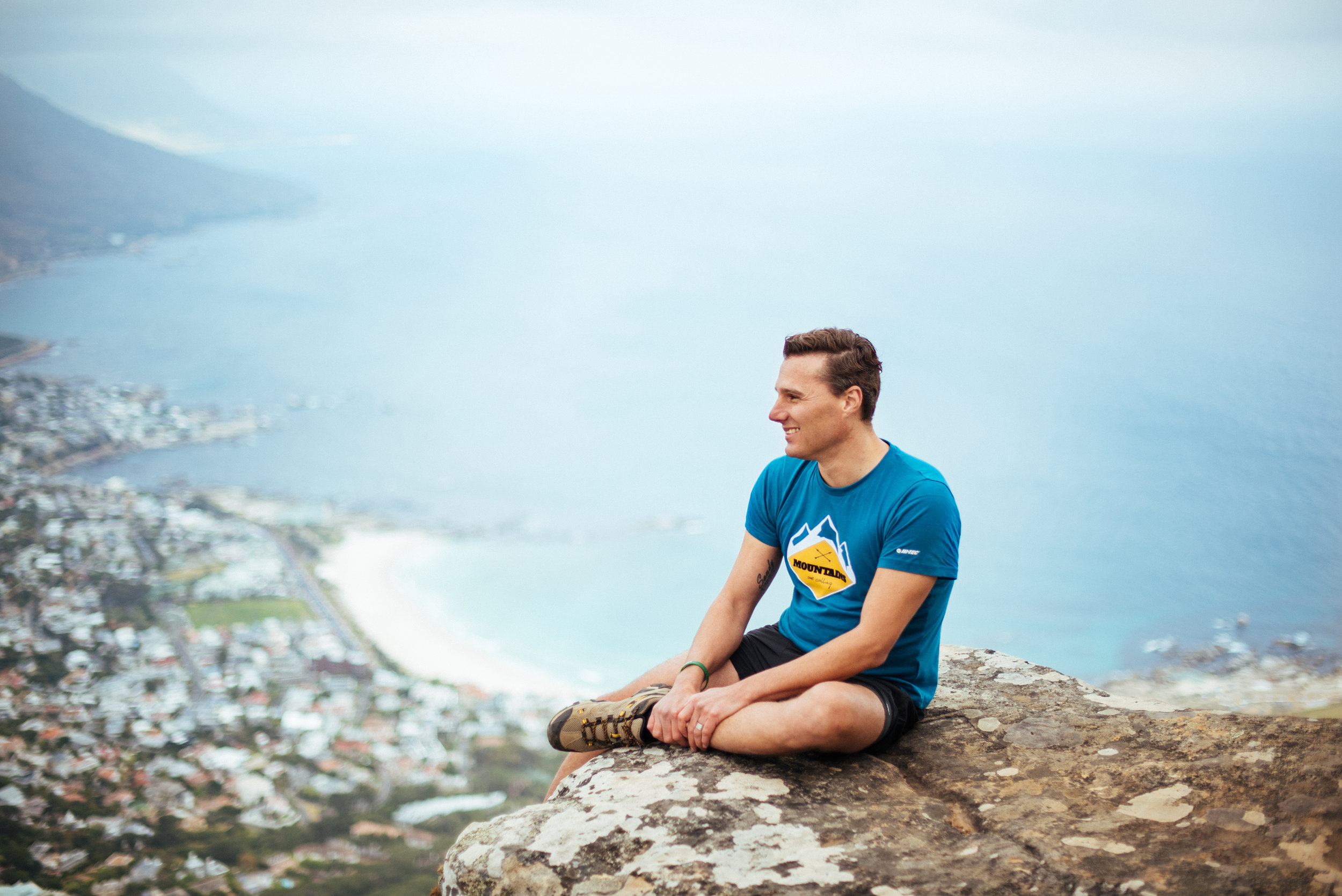 Image of Hein sitting on a ledge on Lionshead overlooking Camps Bay, Cape Town, South Africa