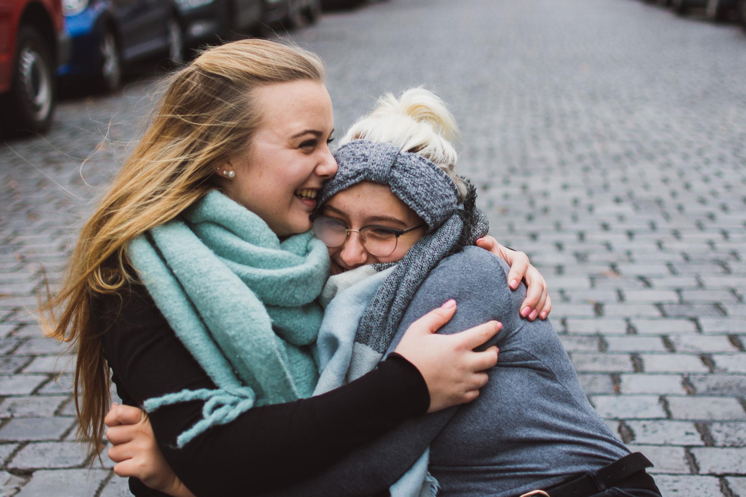 Schwestern-Shooting-Geschwisterliebe-Sitzen-Straße-innige-Umarmung-Witzig.jpg
