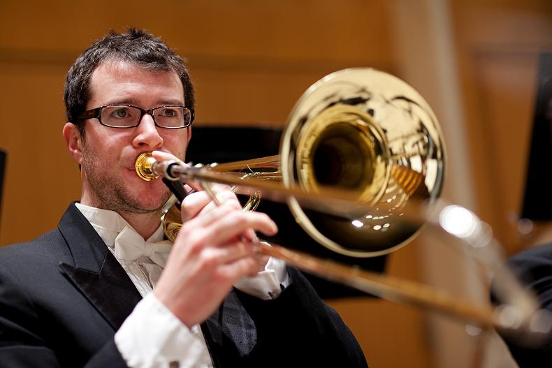 """Trombone - Trombone is the long one without any keys or buttons; instead, it has a long """"slide"""" that the player, yes, slides back and forth to make the instrument longer or shorter (which changes the notes lower or higher). Part of the trombone rests on the player's shoulder, then the big mouthpiece sits over (you guessed it), their mouth, then the slide comes out toward the conductor. Trombone sounds like """"mwomp mwommmmp""""."""